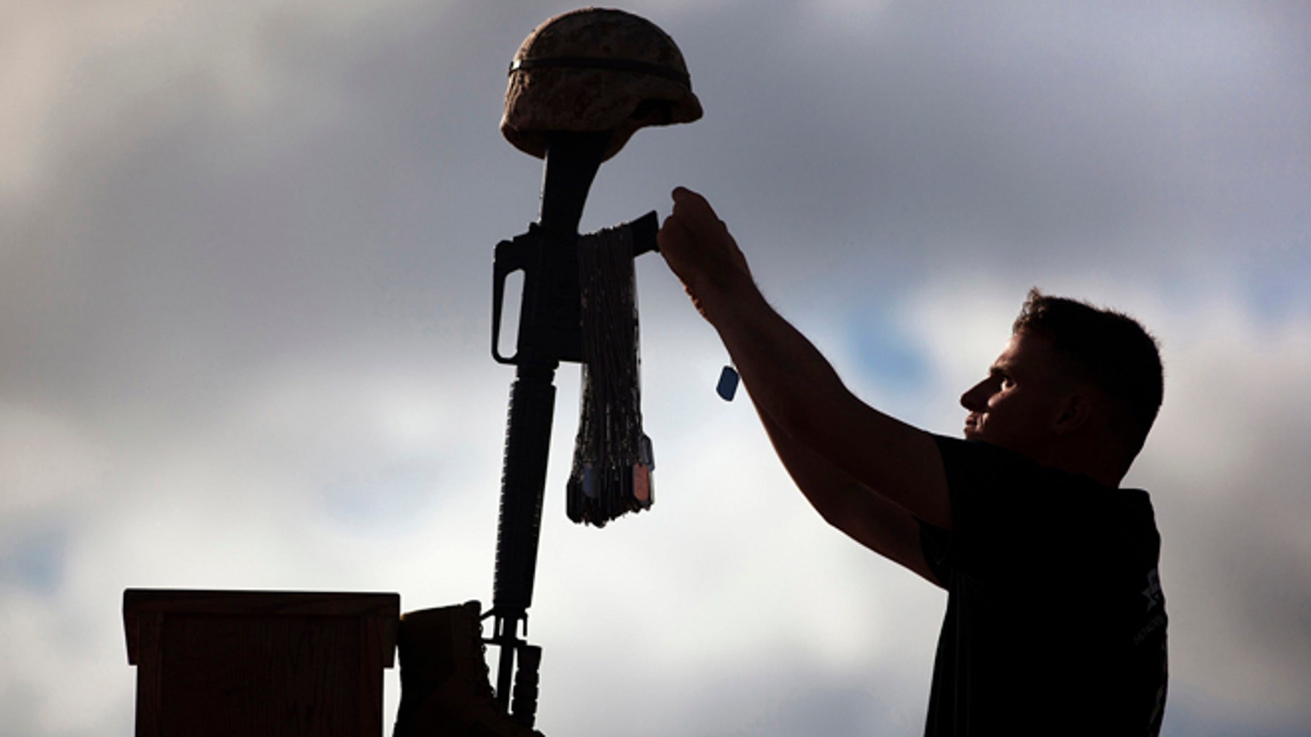 A US Marine places a dog tag of a fallen Marine atop a battlefield cross at a memorial in Hawaii in this 2012 photo.