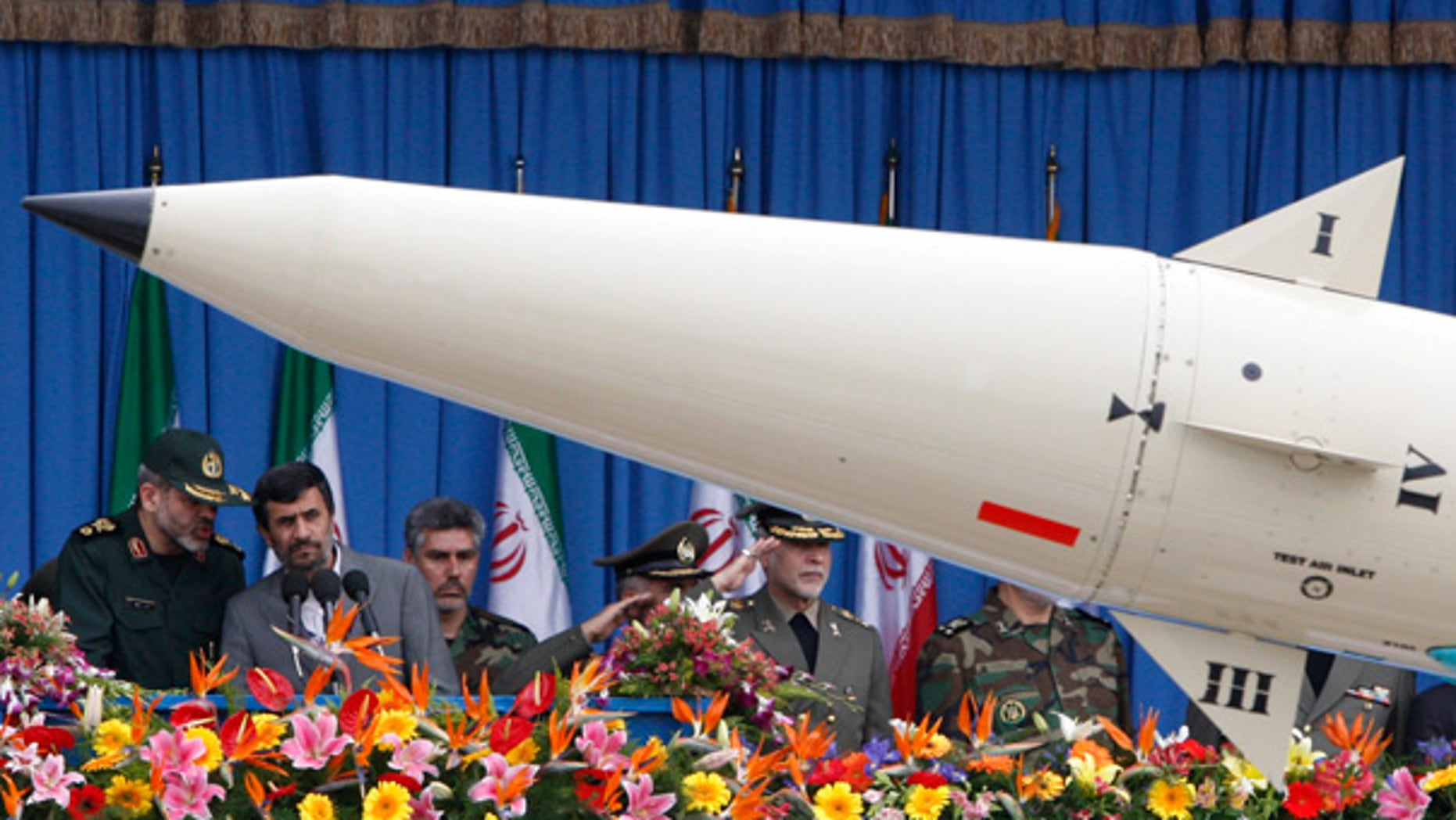 April 18: Iranian President Mahmoud Ahmadinejad, second left, listens to his Defense Minister, Gen. Ahmad Vahidi, as a rocket is paraded during National Army Day.