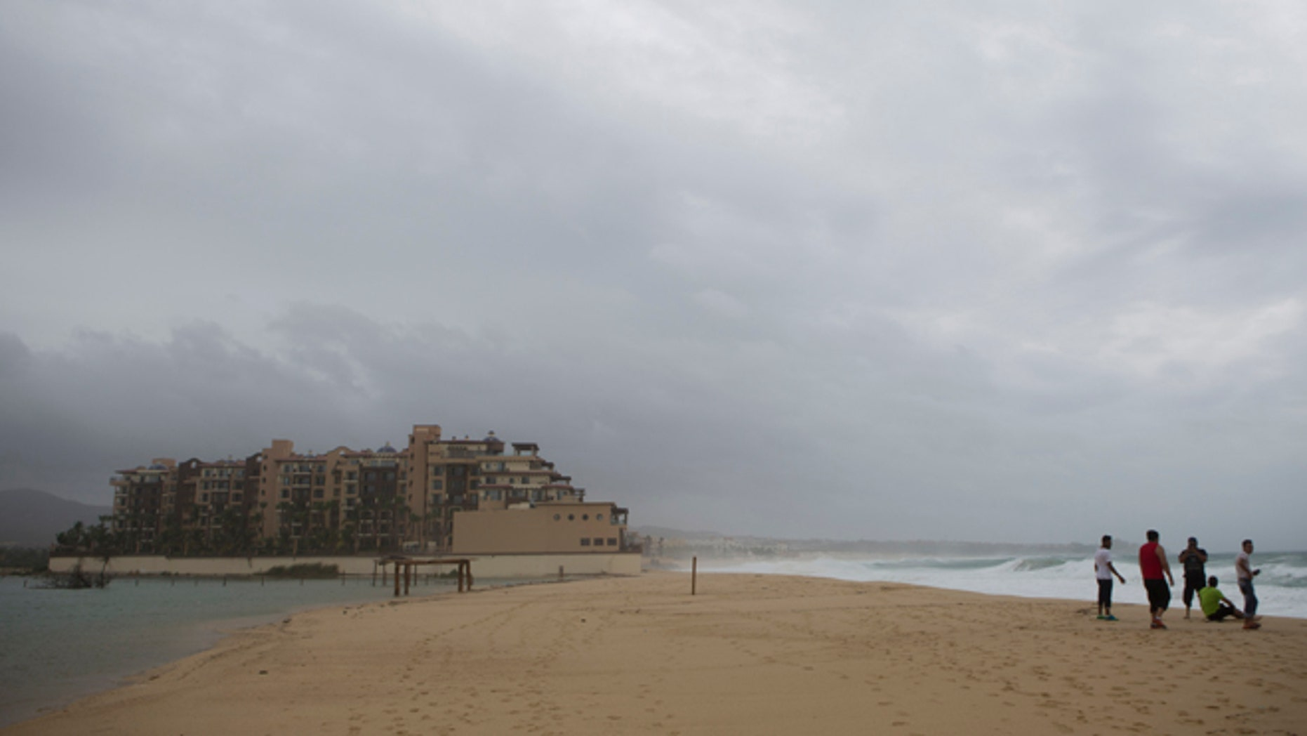 People watch the sea at El Medano Beach before the arrival of Hurricane Blanca, in Cabo San Lucas, Mexico, Sunday June 7, 2015. (AP Photo/Eduardo Verdugo)