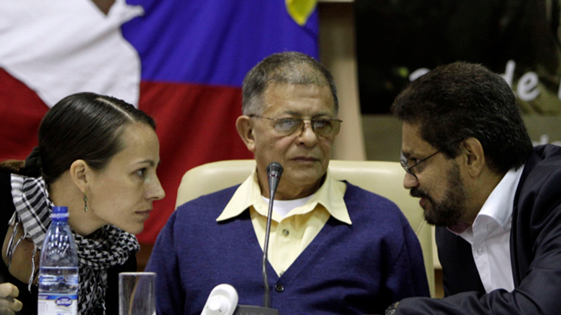 Ivan Marquez, right, chief negotiator for Colombia's Revolutionary Armed Forces of Colombia, or FARC, speaks with Dutch rebel Tanja Nijmeijer as Ricardo Tellez looks on during a press conference in Havana, Cuba, Thursday, Nov. 29, 2012.  After days of intensive peace talks between the FARC and the Colombian government, negotiators will recess and resume talks on Dec. 5. (AP Photo/Franklin Reyes)