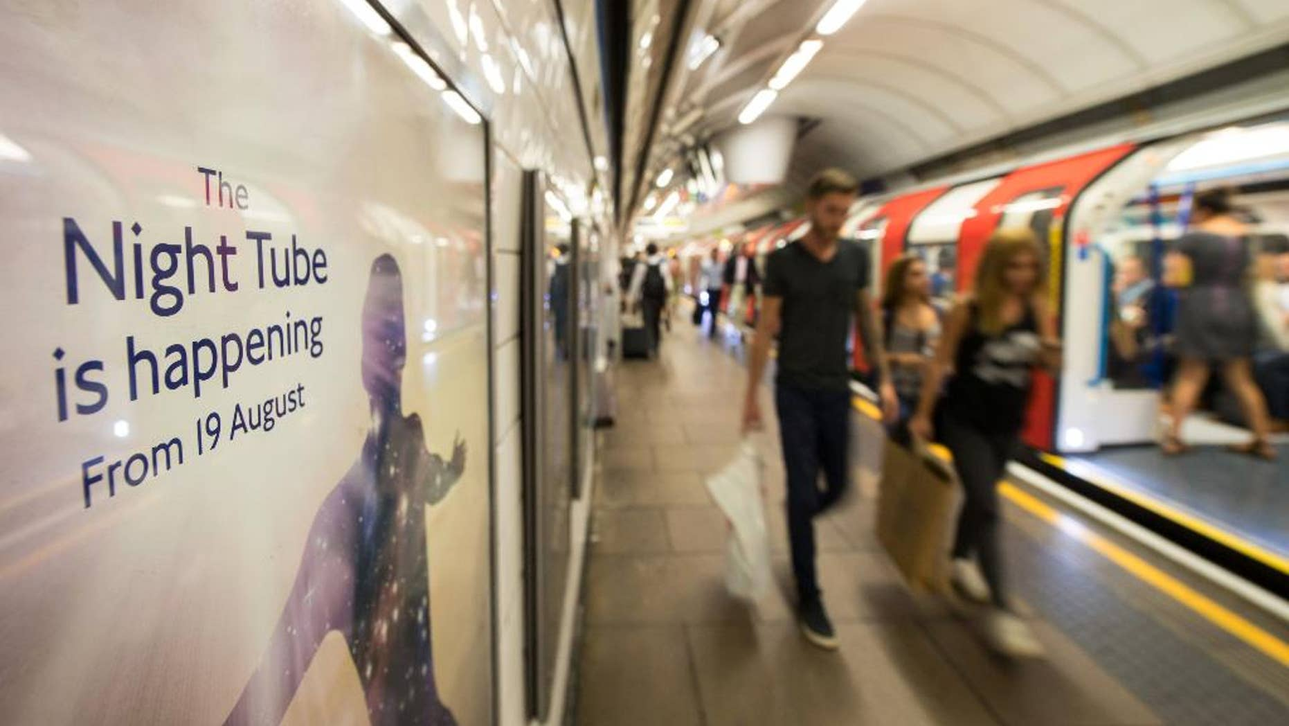 Passengers pass an advert for the night tube on a platform at Oxford Circus underground (tube) station, in London, Wednesday August 17, 2016.  The London underground launches a 'Night Tube' service for the London mass transport system on Friday August 19. (Dominic Lipinski / PA via AP)