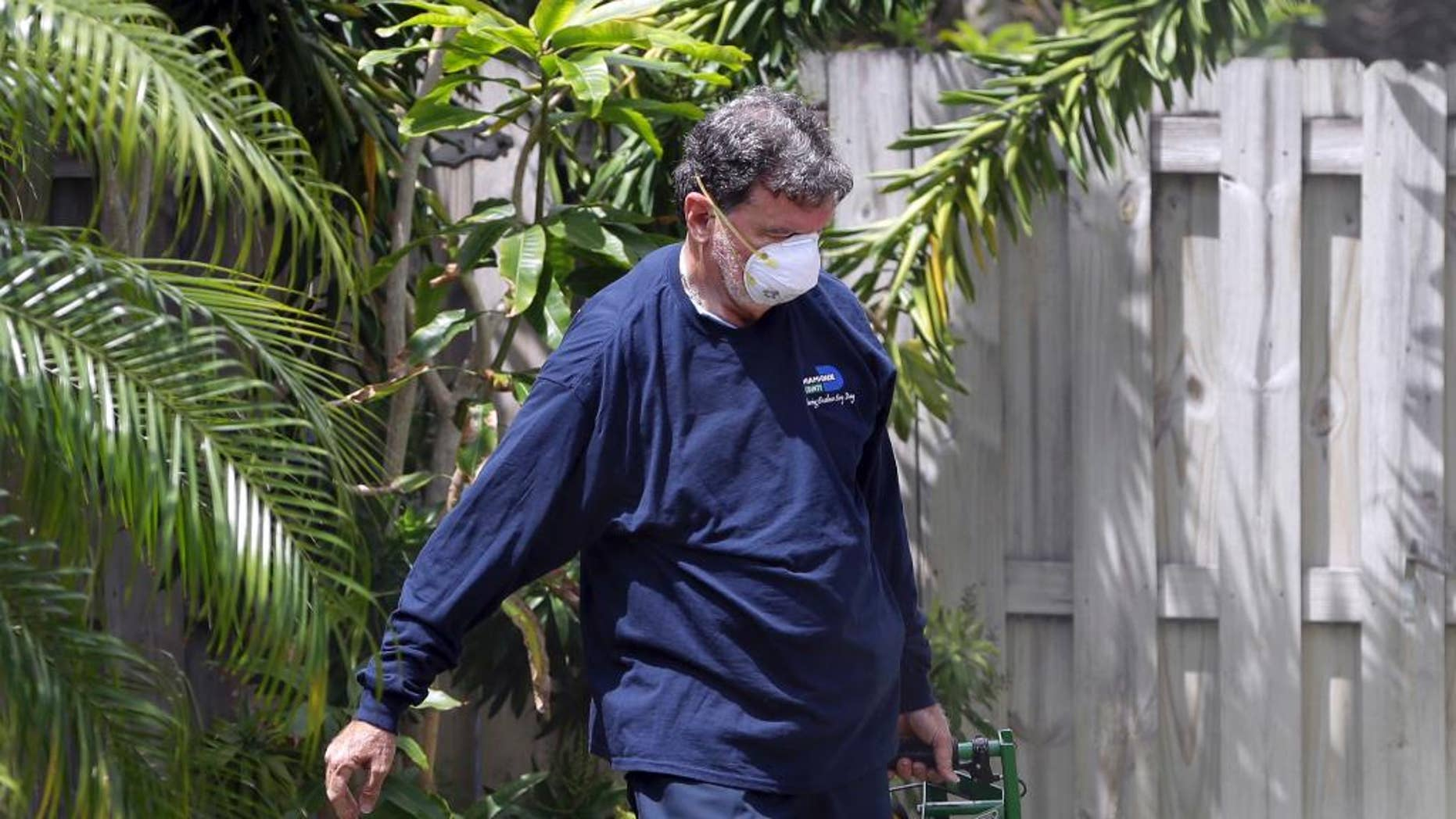 FILE - In this April 12, 2016 photo, Giraldo Carratala, an inspector with the Miami- Dade County, Fla. mosquito control unit, sprays pesticide in the yard of a home in Miami, Fla. On Tuesday, June 14, 2016, health officials announced a plan to combat Zika that includes a special team of experts that can be dispatched to states if the virus spreads in the U.S. Officials aren't expecting big outbreaks of the mosquito-borne virus like in Latin America and the Caribbean. But they do think some U.S. cases are likely as the mosquito season heats up. (AP Photo/Lynne Sladky)