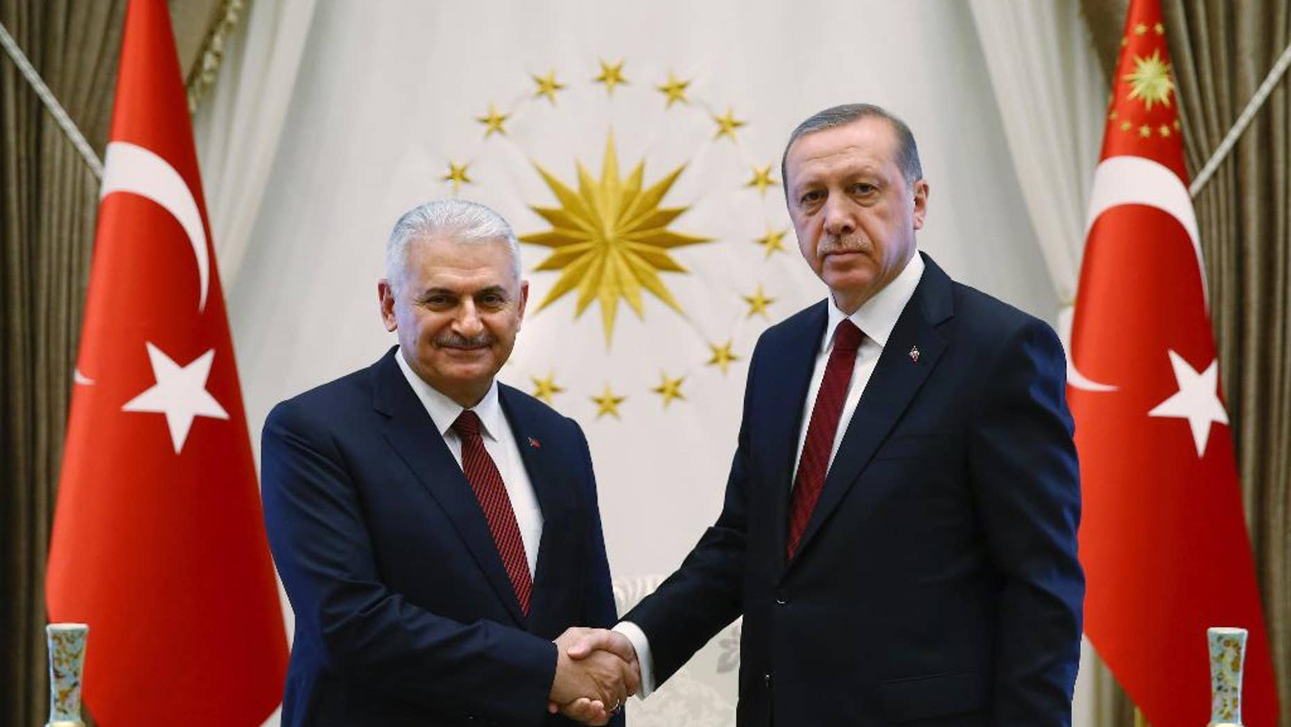 Turkey's President Recep Tayyip Erdogan, right and Turkey's incoming prime minister Binali Yildirim shake hands prior to the government's first cabinet meeting at the Presidential Palace in Ankara, Turkey, Wednesday, May 25, 2016. Erdogan had approved the new government formed by Yildirim, one of his most trusted allies, who immediately asserted the intention to institute constitutional reforms that would expand the powers of the presidency. (Presidential Press Service/Pool Photo via AP)