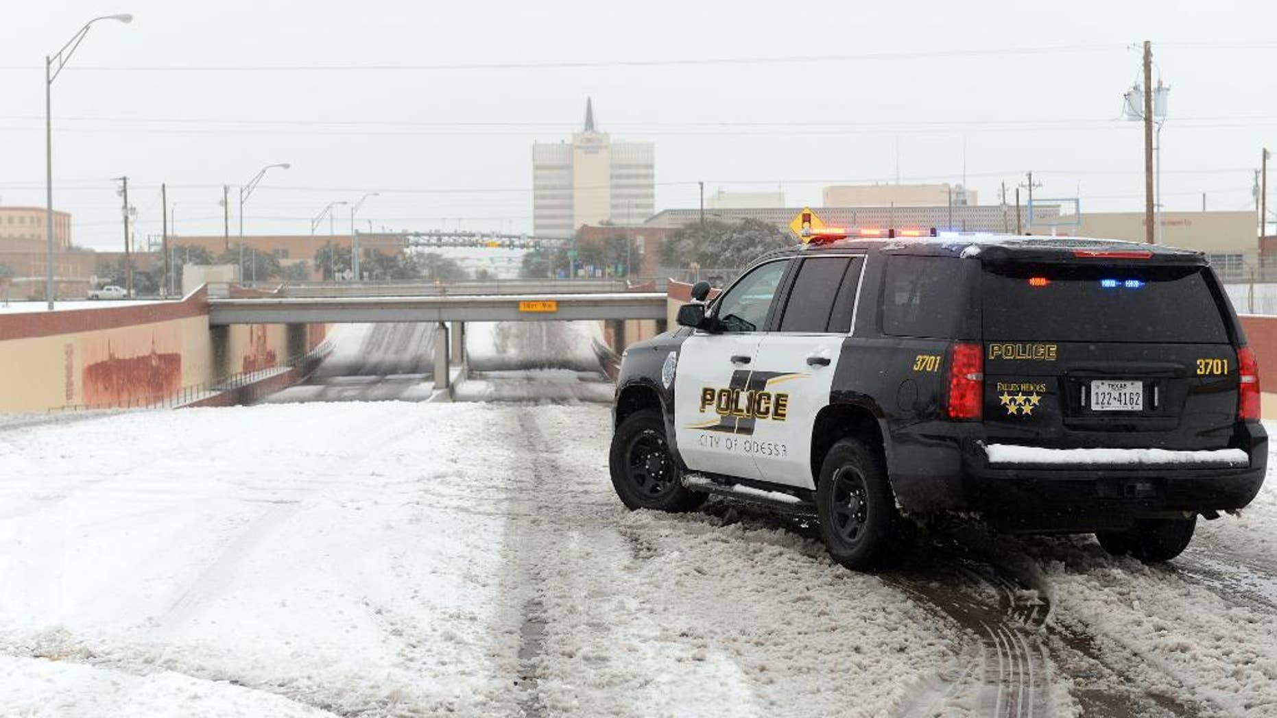 Odessa Police block access to the railroad underpass on Grant Avenue near Second Street, Sunday, Dec. 27, 2015, in Odessa, Texas. Nearly all of Interstate 40 in Texas, the main east-west highway through the Texas Panhandle, has been shut because of the snowstorm pummeling the area. The Texas Department of Public Safety says only a small section of the highway within Amarillo is not closed. (Mark Sterkel/Odessa American via AP) MANDATORY CREDIT