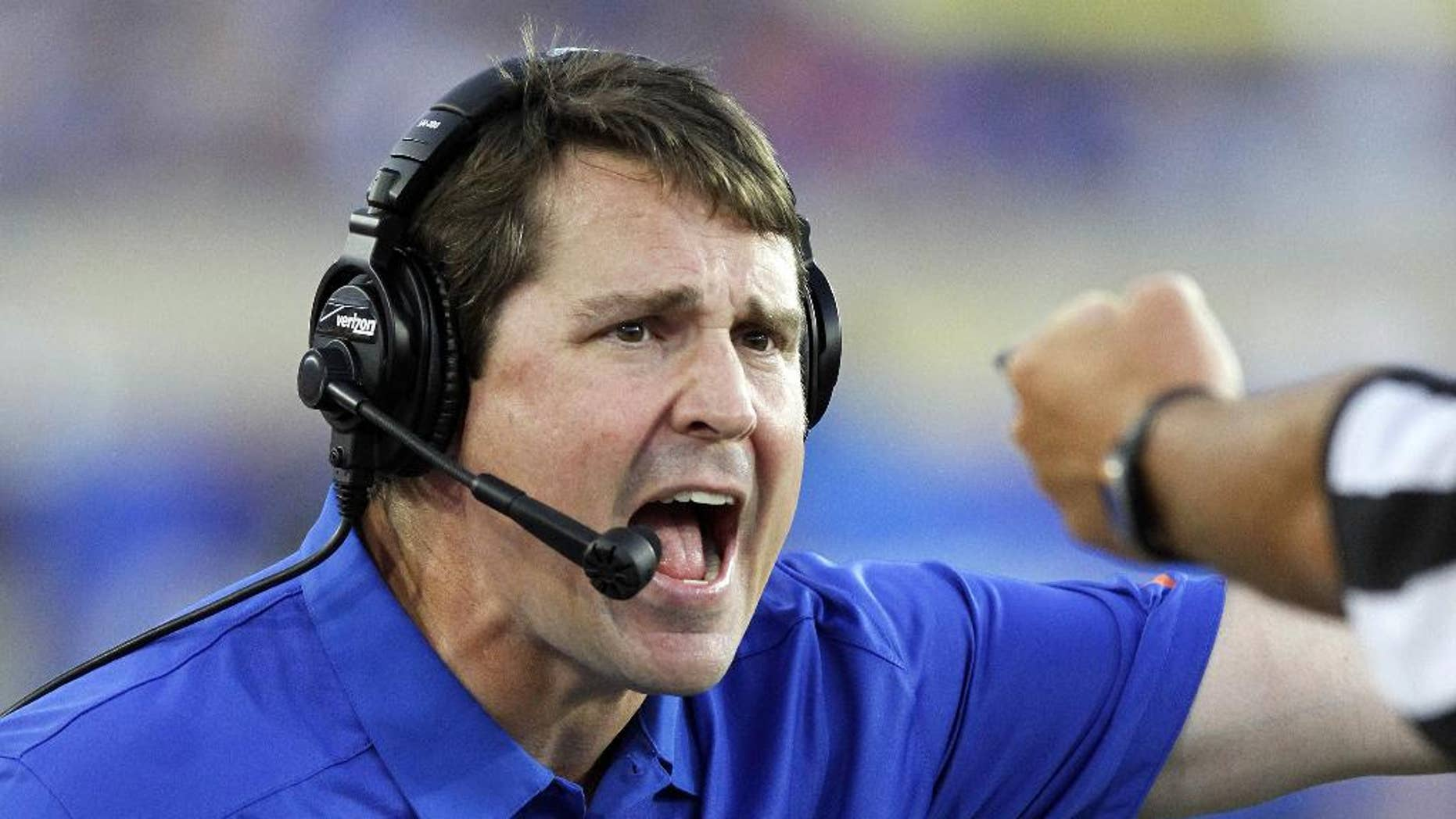 FILE  - In this Sept. 28, 2013, file photo, Florida head coach Will Muschamp yells to an official in the second quarter of an NCAA college football game against Kentucky in Lexington, Ky. Muschamp came to his own defense Wednesday, Sept. 3, 2014, ripping critics who questioned his decision to reinstate three players suspended for a season opener that lasted just 10 seconds. (AP Photo/James Crisp, File)