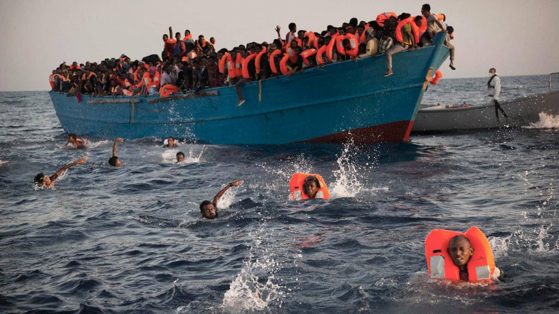 FILE - In this Aug. 29, 2016 file photo, migrants, most from Eritrea, jump into the water from a crowded wooden boat as they are helped by members of a nongovernmental organization during a rescue operation in the Mediterranean Sea, about 13 miles (20 kilometers) north of Sabratha, Libya. A new EU report accessed by The Associated Press on Thursday, Dec. 1, 2016, says that Libya's coastal cities are generating up to 325 million euros ($346 million) in revenue each year from people smuggling. (AP Photo/Emilio Morenatti, File)