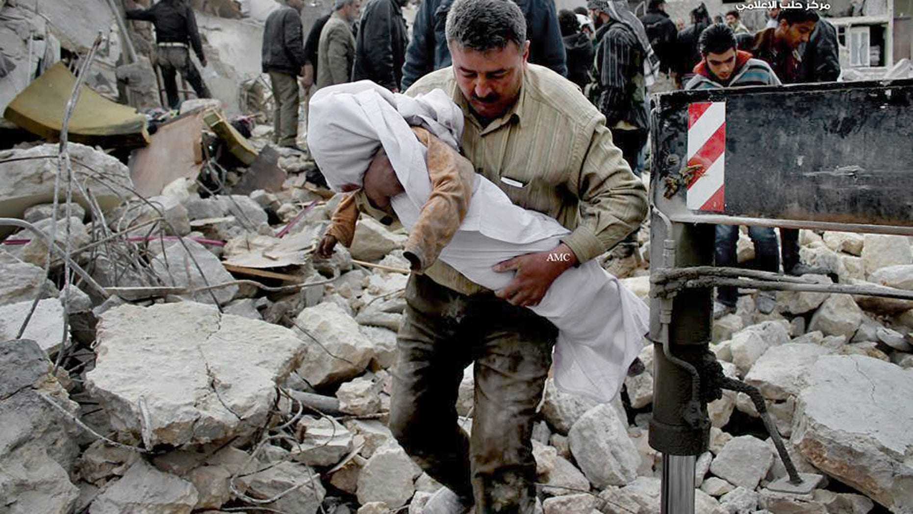 In this Wednesday, Jan. 29, 2014 citizen journalism image provided by Aleppo Media Center (AMC), an anti-Bashar Assad activist group, which has been authenticated based on its contents and other AP reporting, shows a Syrian man carrying the body of a child who was killed following a Syrian government airstrike in Aleppo, Syria. (AP Photo/Aleppo Media Center, AMC)