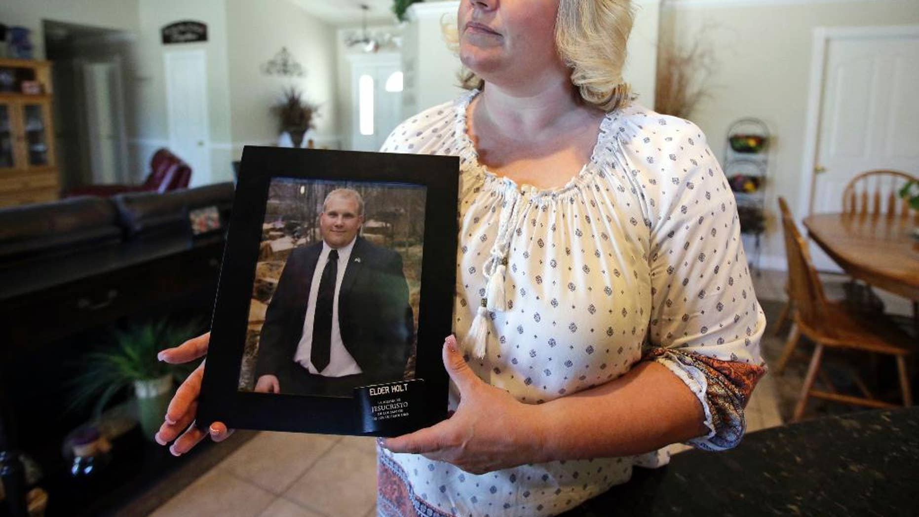FILE - In this July 13, 2016 file photo, Laurie Holt holds a photograph of her son Joshua Holt at her home, in Riverton, Utah. Joshua Holt jailed in Venezuela since June has had his hopes for being reunited with his family for Christmas all but dashed with the fourth postponement of a preliminary hearing. Judge Elena Cassiani did not appear for a Tuesday, dec. 6, 2016 hearing, in which she was to rule on whether to dismiss the weapons charges against Holt. A new date was set for January. (AP Photo/Rick Bowmer, File)