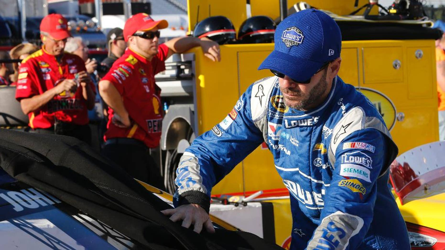 Jimmie Johnson takes a cover off his car prior to qualifying for Saturday's NASCAR Sprint Cup auto race at Richmond International Raceway in Richmond, Va., Friday, Sept. 11, 2015. (AP Photo/Steve Helber)