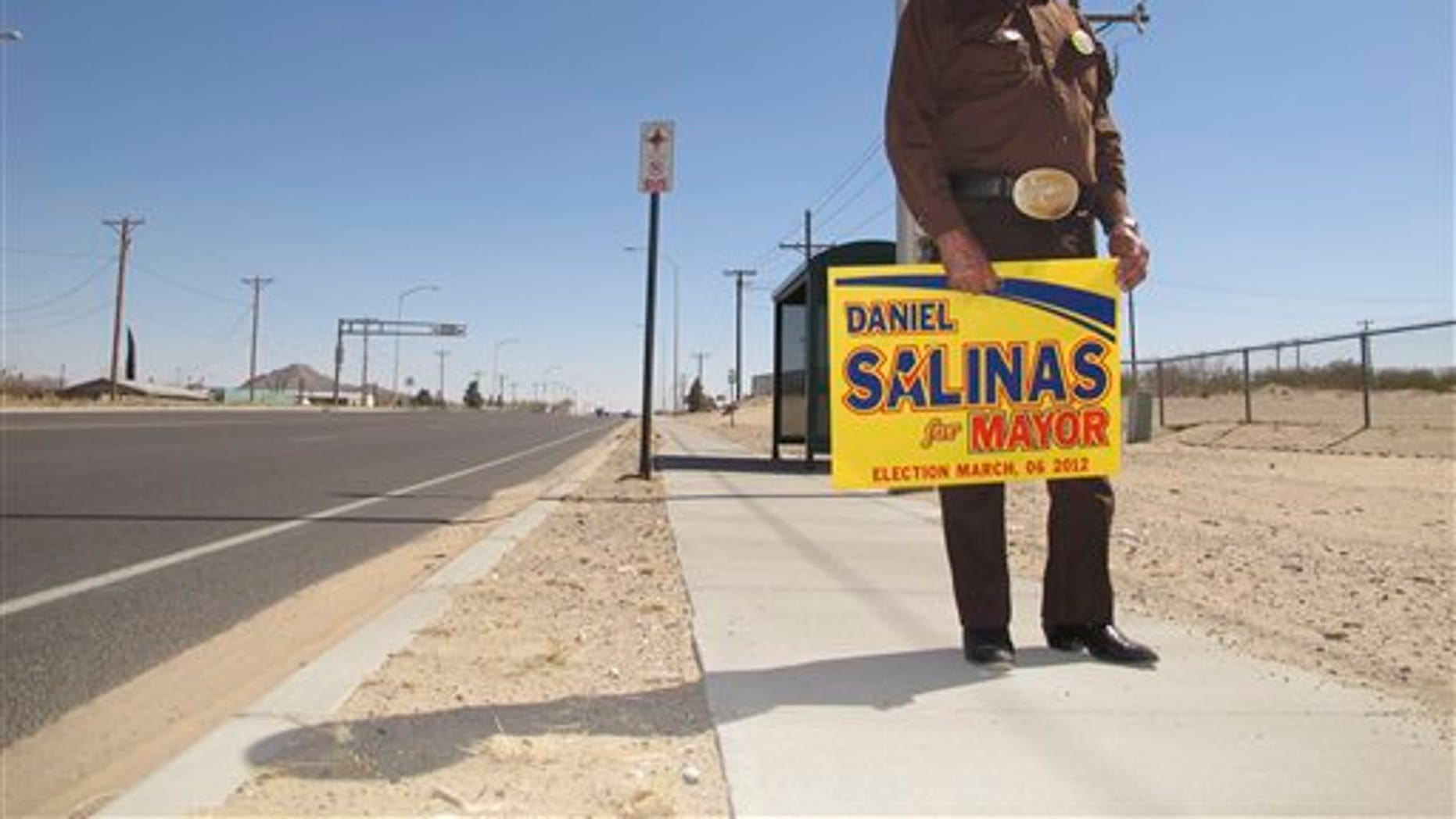 Everardo Holguin, 75, stands with a poster supporting his candidate for mayor Tuesday March. 6, 2012, in Sunland Park, New Mexico. The city of 14,000 inhabitants has undergone a turbulent mayoral campaign with candidate Gerardo Hernandez involved in a sex scandal and Mayor-elect Daniel Salinas facing charges of extorting his rival and a city official. (AP Photo/Juan Carlos Llorca)