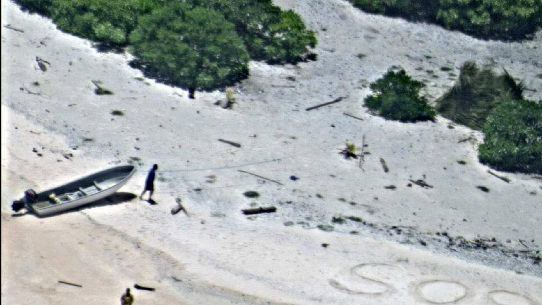 """In this Aug. 25, 2016, photo provided by the U.S. Navy, a pair of stranded mariners signal for help as a U.S. Navy P-8A Poseidon aircraft crew from Patrol Squadron (VP) 8 flies over in support of a Coast Guard search and rescue mission on an uninhabited island in Micronesia, Hawaii. The U.S. Coast Guard says the two stranded mariners were rescued Friday after crews saw their """"SOS"""" in the sand. (U.S. Navy via AP)"""