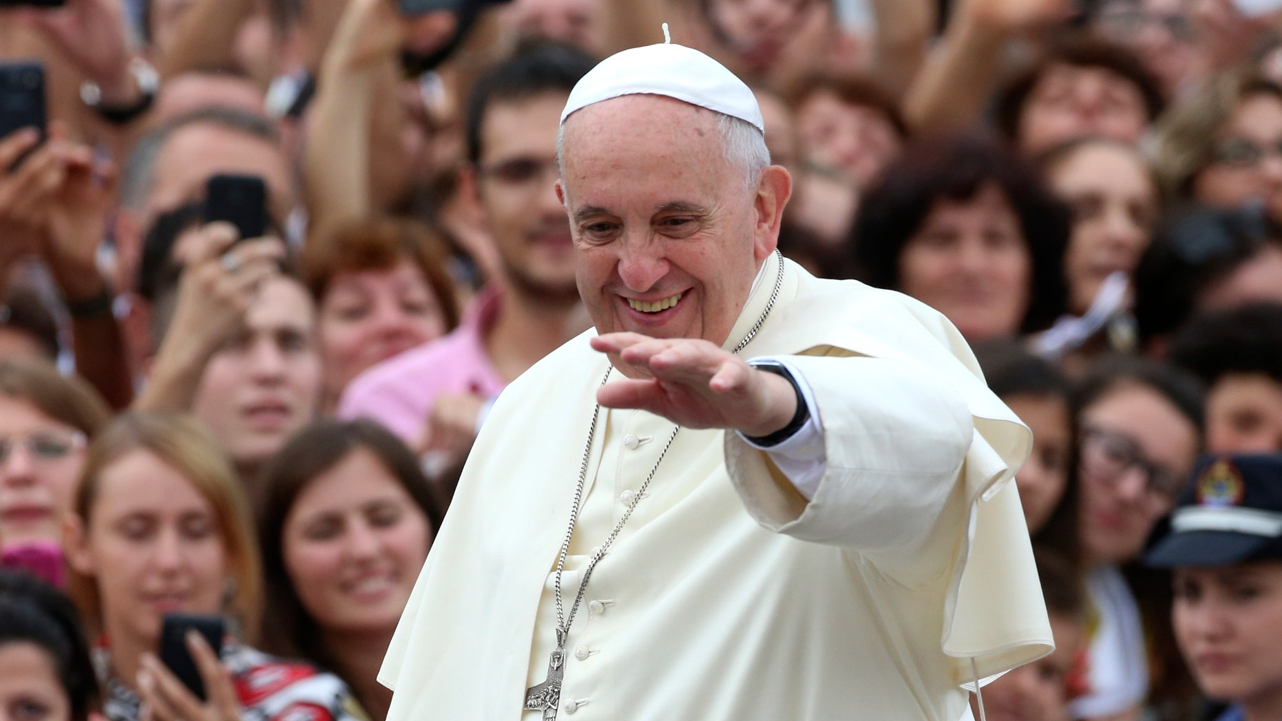 Pope Francis waves to faithful as he is driven through the crowd, in Mother Teresa Square, in Tirana, Sunday, Sept. 21, 2014. Pope Francis arrived Sunday in Albania on his first European trip, designed to highlight the Balkan nation's path from a brutal communist state where religion was banned to a model of Christian-Muslim coexistence for a world witnessing conflict in God's name. (AP Photo/Hector Pustina)