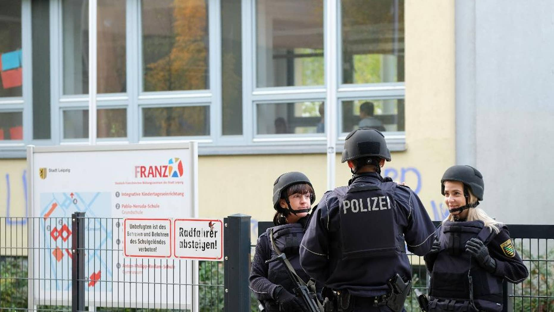 Police stand in front of the Reclam High School in Leipzig, Germany, Monday Oct. 17, 2016.  Police say that schools in at least two German cities have received threats and authorities are working to figure out who and what is behind them. Police in Leipzig said at least seven schools in Leipzig received threats by emails on Monday, though it wasn't clear exactly what was threatened, news agency dpa reported. Officers were sent to the schools, and students and teachers had to remain in the buildings.  ( Sebastian Willnow/dpa via AP)