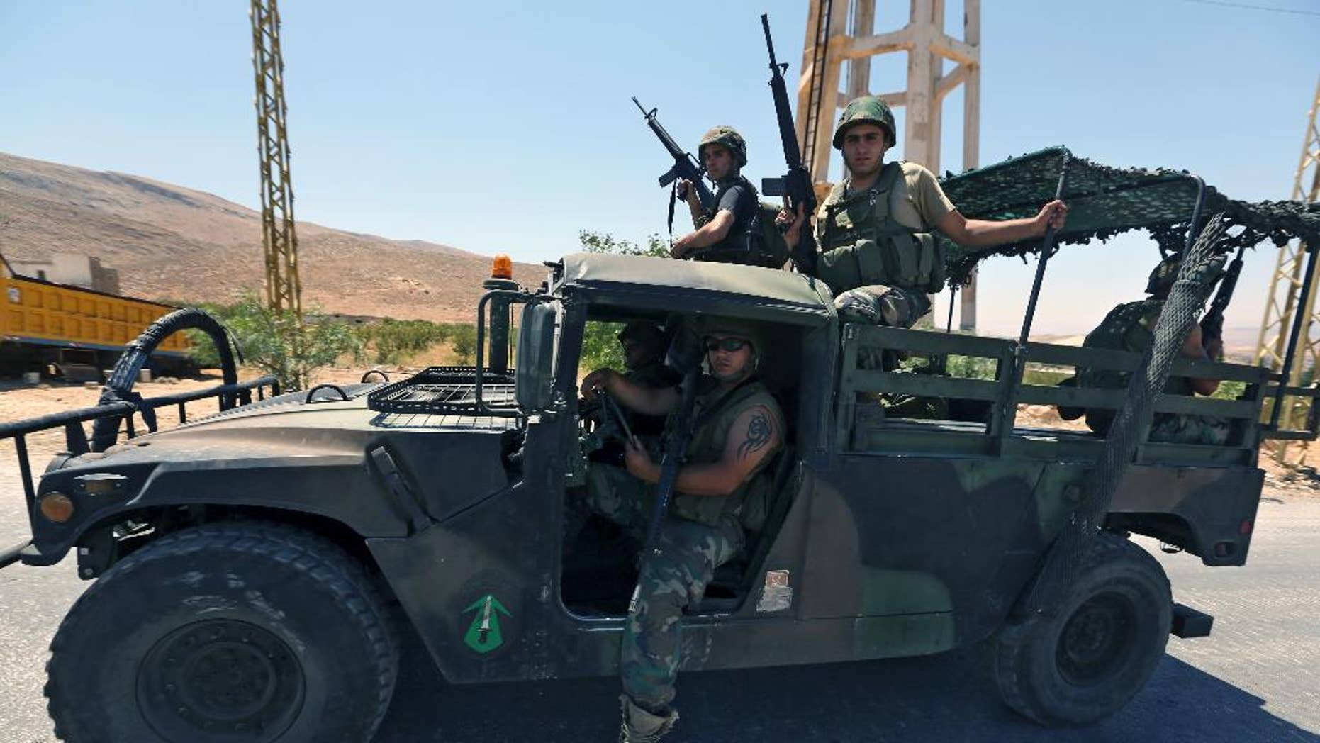 Lebanese army soldiers sit inside a Humvee as reinforcements arrive to the outskirts of Arsal, a predominantly Sunni Muslim town near the Syrian border in eastern Lebanon, Monday, Aug. 4, 2014. Thousands of Lebanese civilians and Syrian refugees packed cars and pickup trucks Monday, fleeing an eastern border town that was overrun by militants from neighboring Syria as Lebanese troops fight to liberate the area. (AP Photo/Bilal Hussein)