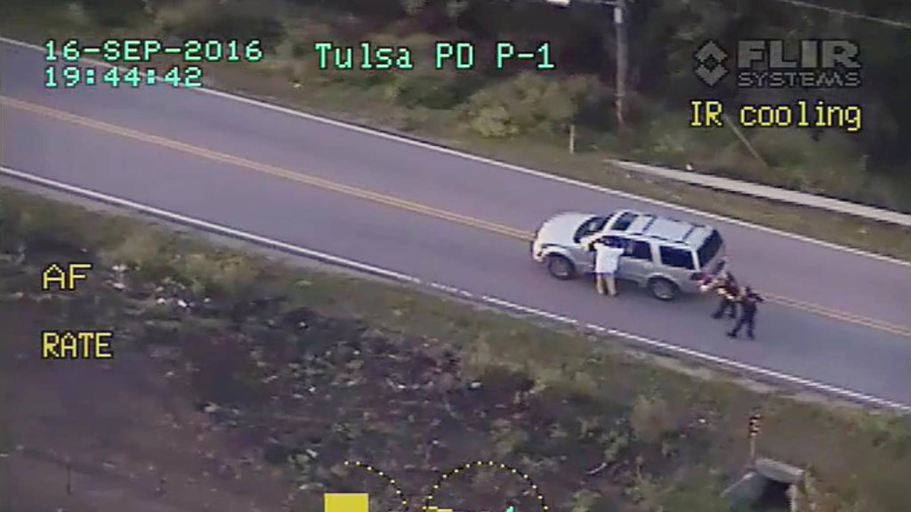 FILE - In this photo made from a Sept. 16, 2016 police video, Terence Crutcher, left, with his arms up is pursued by police officers as he walks next to his stalled SUV moments before he was shot and killed by one of the officers in Tulsa, Okla. Recent shootings by police raise a fundamental question: In the moments after officers shoot someone, how soon can medical aid be given? (Tulsa Police Department via AP, File)