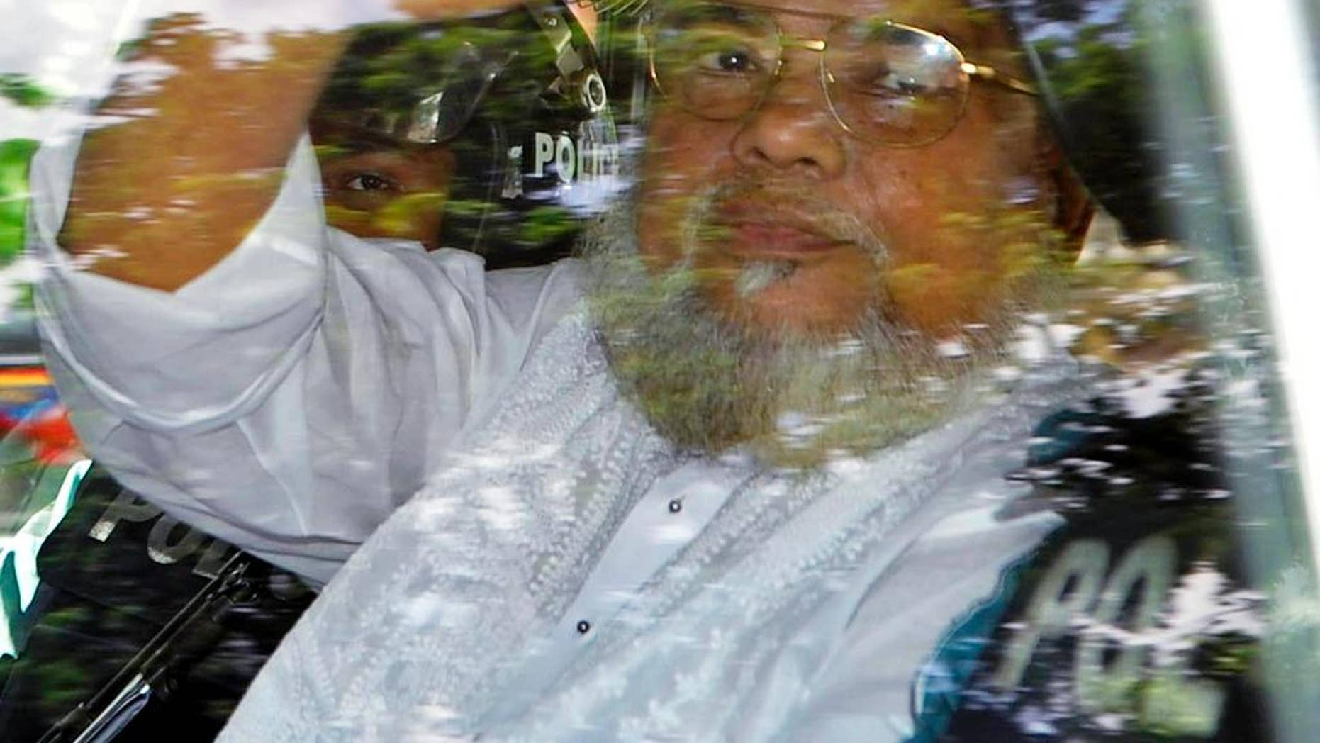 FILE - In this July 17, 2013, file photo, Ali Ahsan Mohammad Mojaheed, the secretary-general of Bangladesh's Jamaat-e-Islami party, waves from a police vehicle as he is brought to court in Dhaka, Bangladesh. Bangladesh's Supreme Court on Tuesday, June 16, 2015, upheld his death sentence for war crimes and crimes against humanity during the country's independence war against Pakistan in 1971. (AP Photo, File)