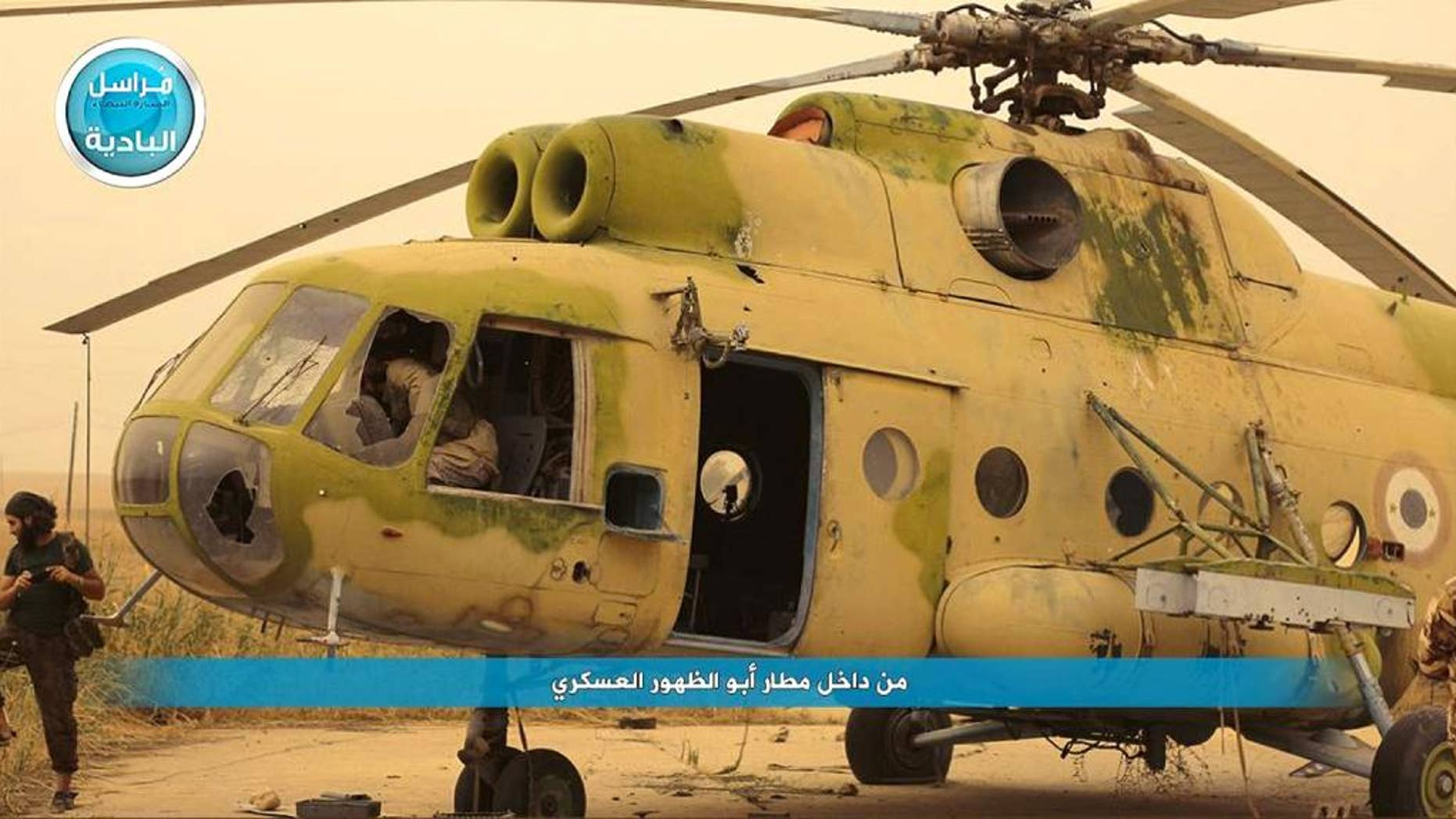 """In this image posted on a social media account of Syria's al-Qaida-linked Nusra Front early Thursday Sept. 10, 2015, which is consistent with AP reporting, shows fighters from the group in and around a Syrian government forces helicopter, inside the Abu Zuhour air base, in Idlib province, north Syria. After a two-year siege, al-Qaida's affiliate in Syria and other insurgents on Wednesday captured the one remaining Syrian army air base in Idlib province, a development that activists said effectively expelled the last of President Bashar Assad's military from the northwestern province. The Arabic words read: """"from inside Abu Zuhour air base."""" (Al-Nusra Front social media account via AP)"""