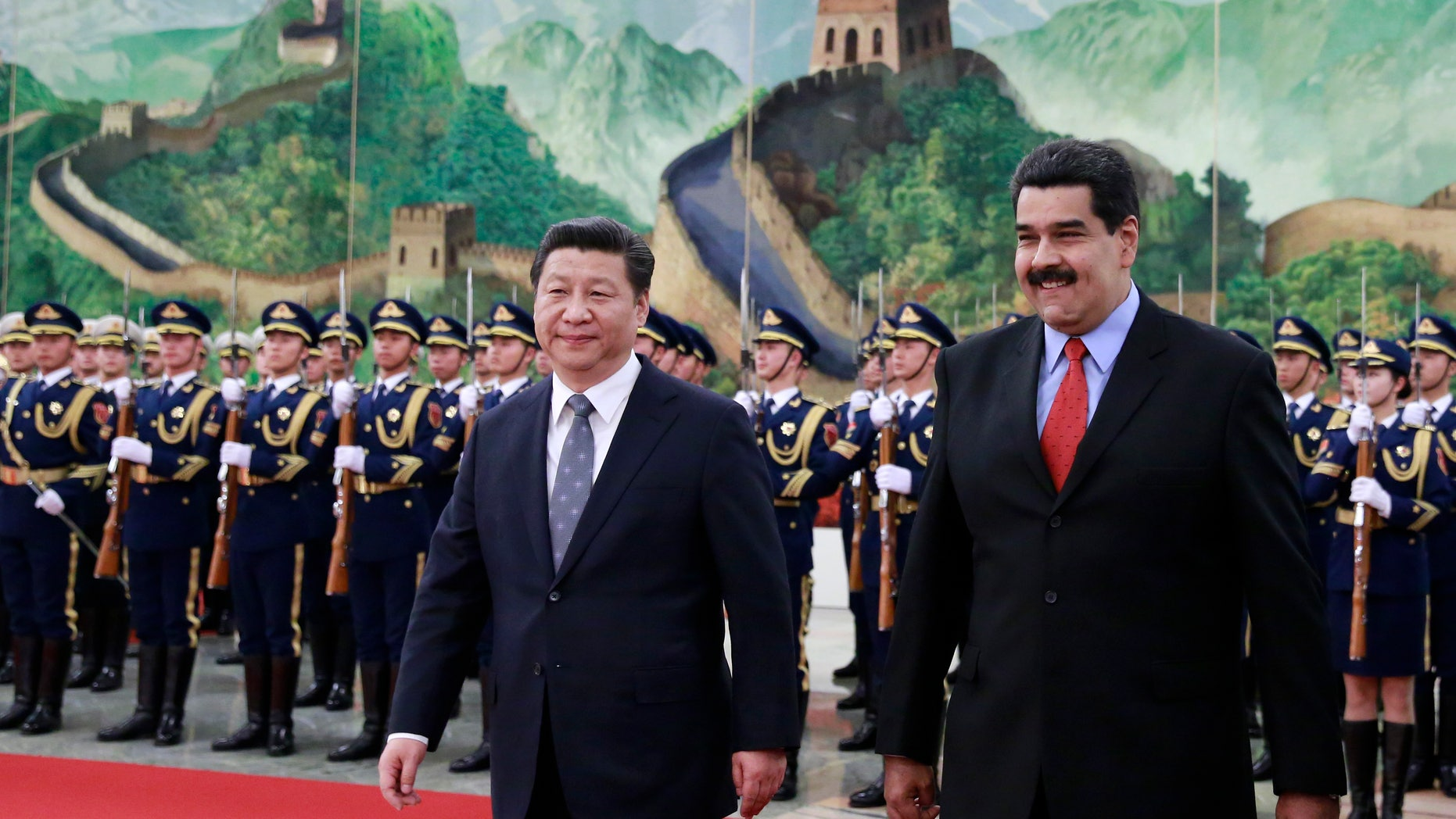 Venezuela's President Nicolas Maduro, right, walks with Chinese President Xi Jinping during a welcome ceremony at the Great Hall of the People in Beijing, China Wednesday, Jan. 7, 2015. (AP Photo/Andy Wong, Pool)