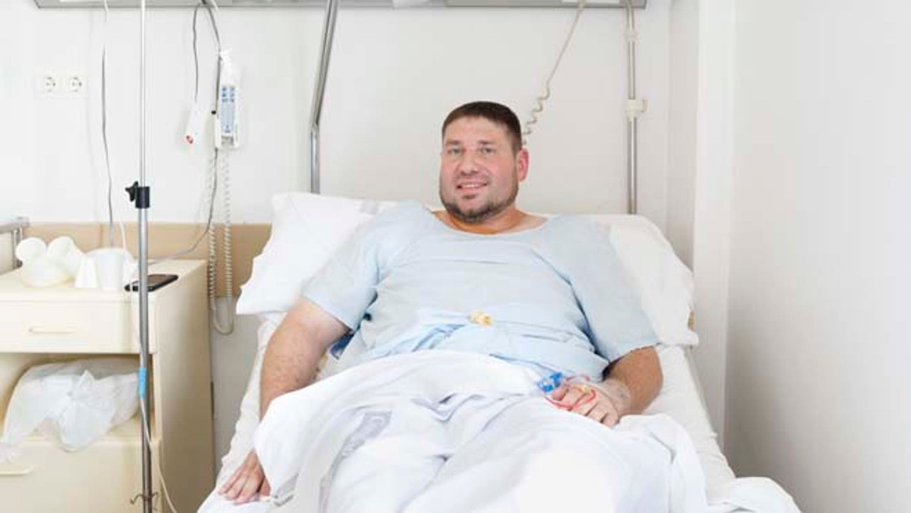 Mike Webster, a 38-year-old occupational therapist from Gainesville, Florida, who was gored in the armpit while running with the bulls in Pamplona for the 38th time over the last 11 years, poses for a picture on his hospital bed in Pamplona, Spain, Tuesday, July 7, 2015. Two Americans and a Briton were gored and eight others injured Tuesday as thousands of daredevils dashed alongside fighting bulls through the streets of this northern Spanish city on the first bull run of the San Fermin festival (AP Photo/Daniel Ochoa de Olza)
