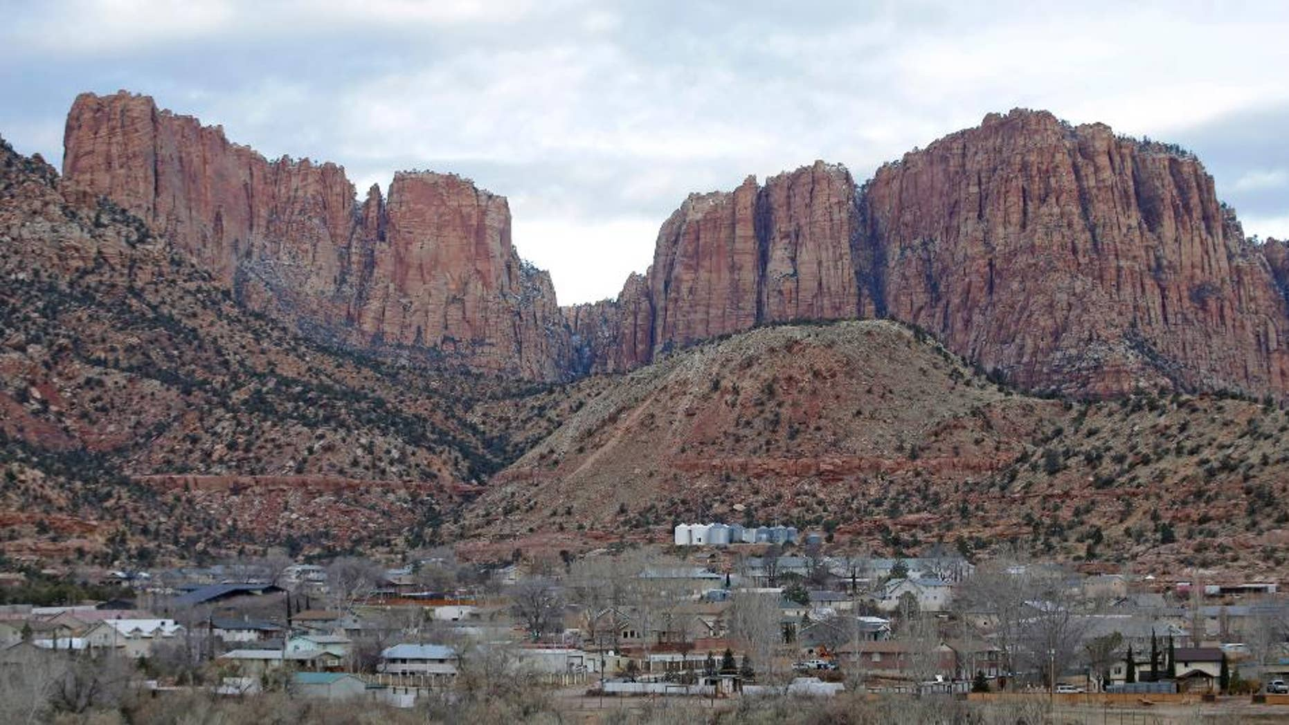 FILE - This Dec. 16, 2014, file photo, shows Hildale, Utah, sitting at the base of Red Rock Cliff mountains, with its sister city, Colorado City, Ariz., in the foreground. The federal government's bid to dismantle the police department in a polygamous community on the Arizona-Utah border has been rejected by a judge as too drastic and expensive. But the towns will still be under court supervision for the next decade as punishment in a religious discrimination case. (AP Photo/Rick Bowmer, File)