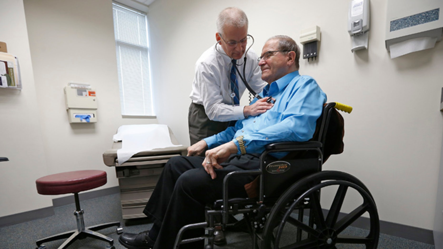 FILE: A doctor treats a patient at his office in Peoria, Illinois.