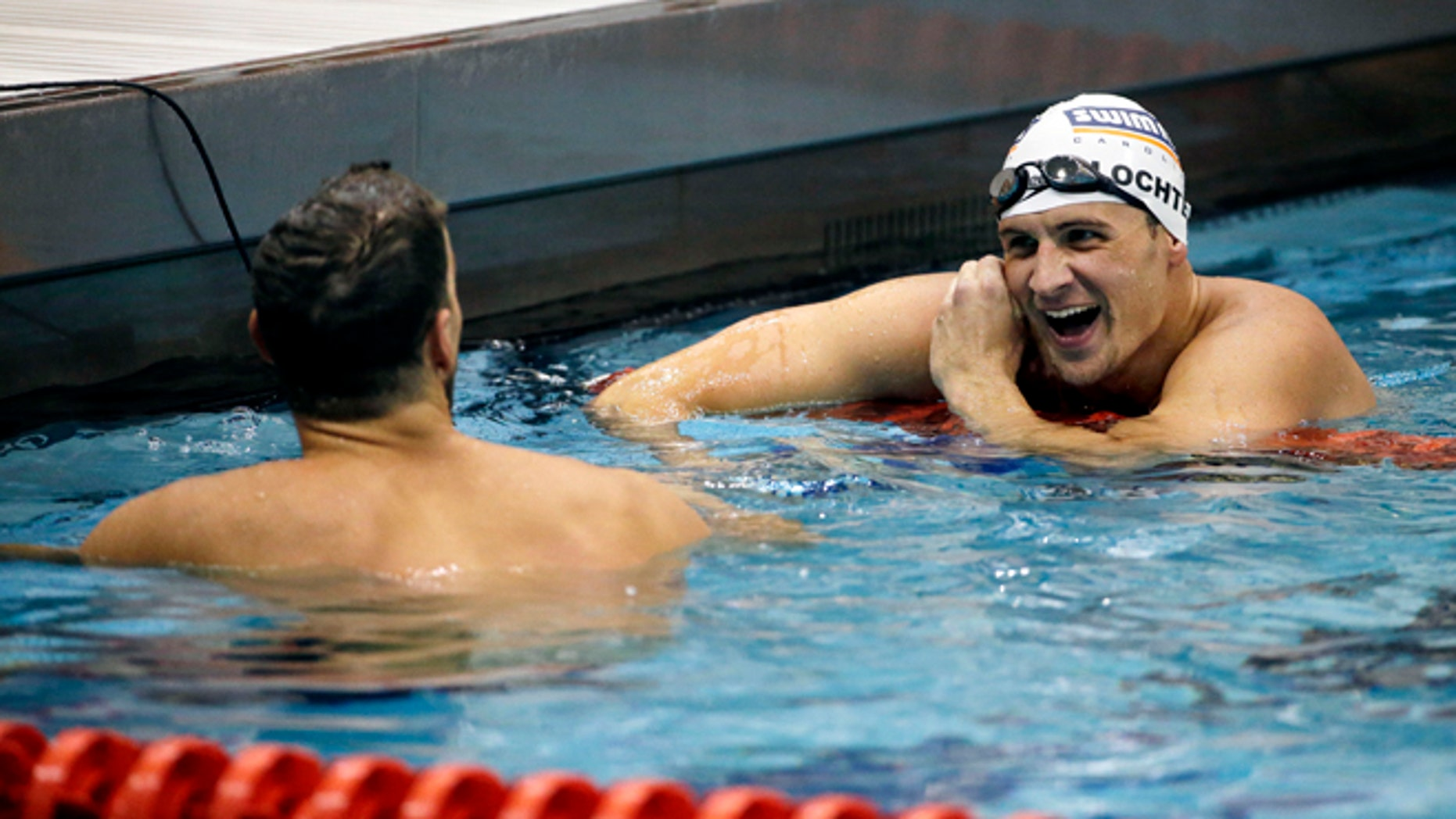 Michael Phelps, left, talks with Ryan Lochte, right, after Phelps beat Lochte to win the men's 100-meter backstroke at the Bulldog Grand Slam swim meet at the University of Georgia, Saturday, July 12, 2014, in Athens, Ga. Lochte took second place in the event. (AP Photo/David Goldman)