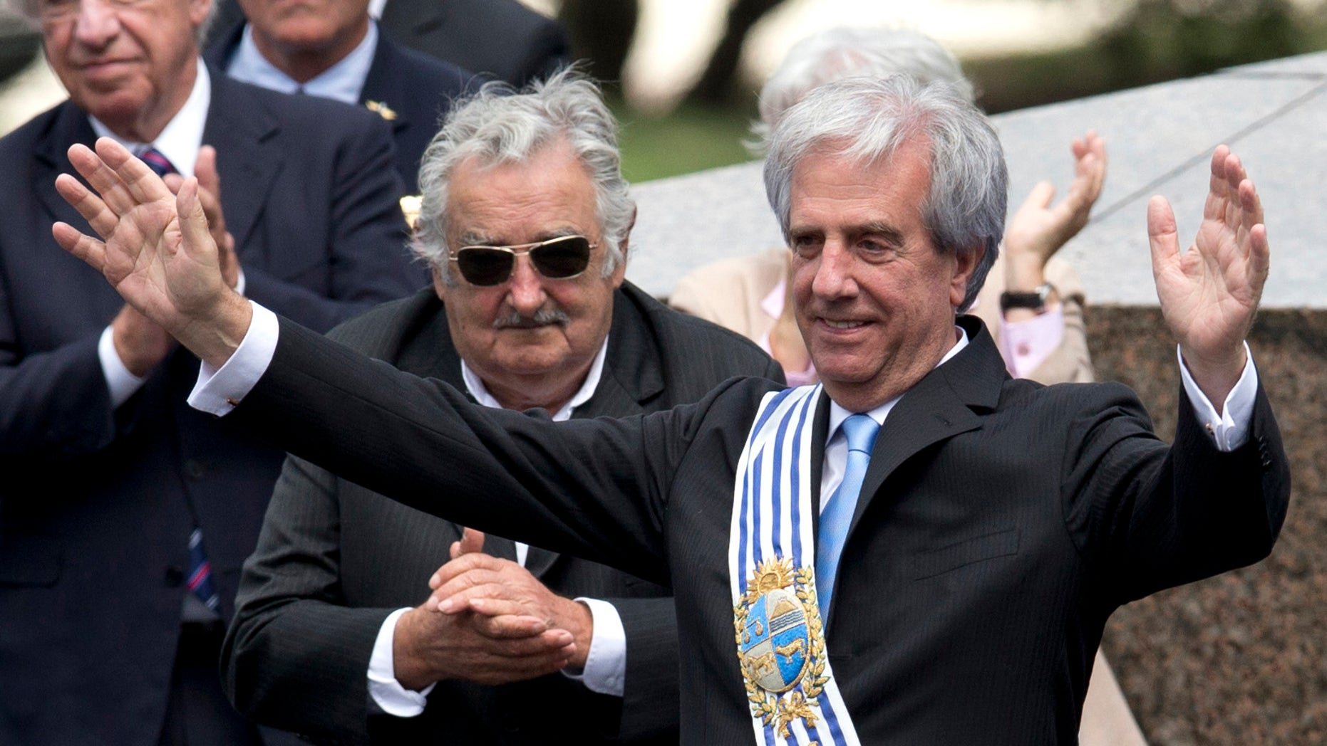 Uruguay's new President Tabare Vazquez waves to the crowd wearing the presidential sash as outgoing President Jose Mujica looks on, behind center, during his inauguration ceremony at Independence Plaza in Montevideo, Uruguay, Sunday, March 1, 2015. (AP Photo/Natacha Pisarenko)
