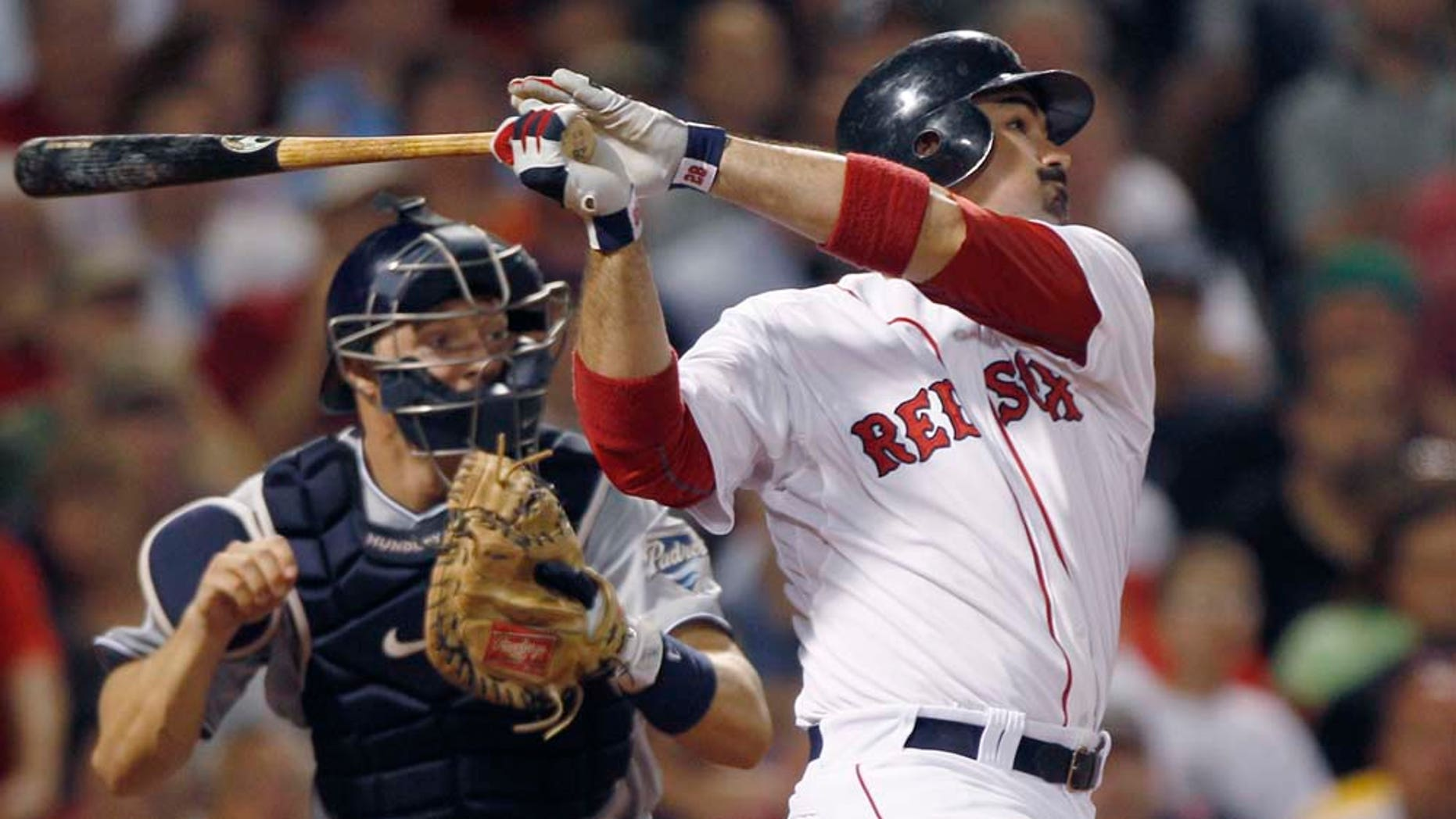 Boston Red Sox Adrian Gonzalez, right, and San Diego Padres catcher Nick Hundley watch Gonzalez's RBI double, breaking a 3-3 tie, in the bottom of the seventh inning of an interleague baseball game at Fenway Park in Boston, Monday, June 20, 2011. (AP Photo/Charles Krupa)