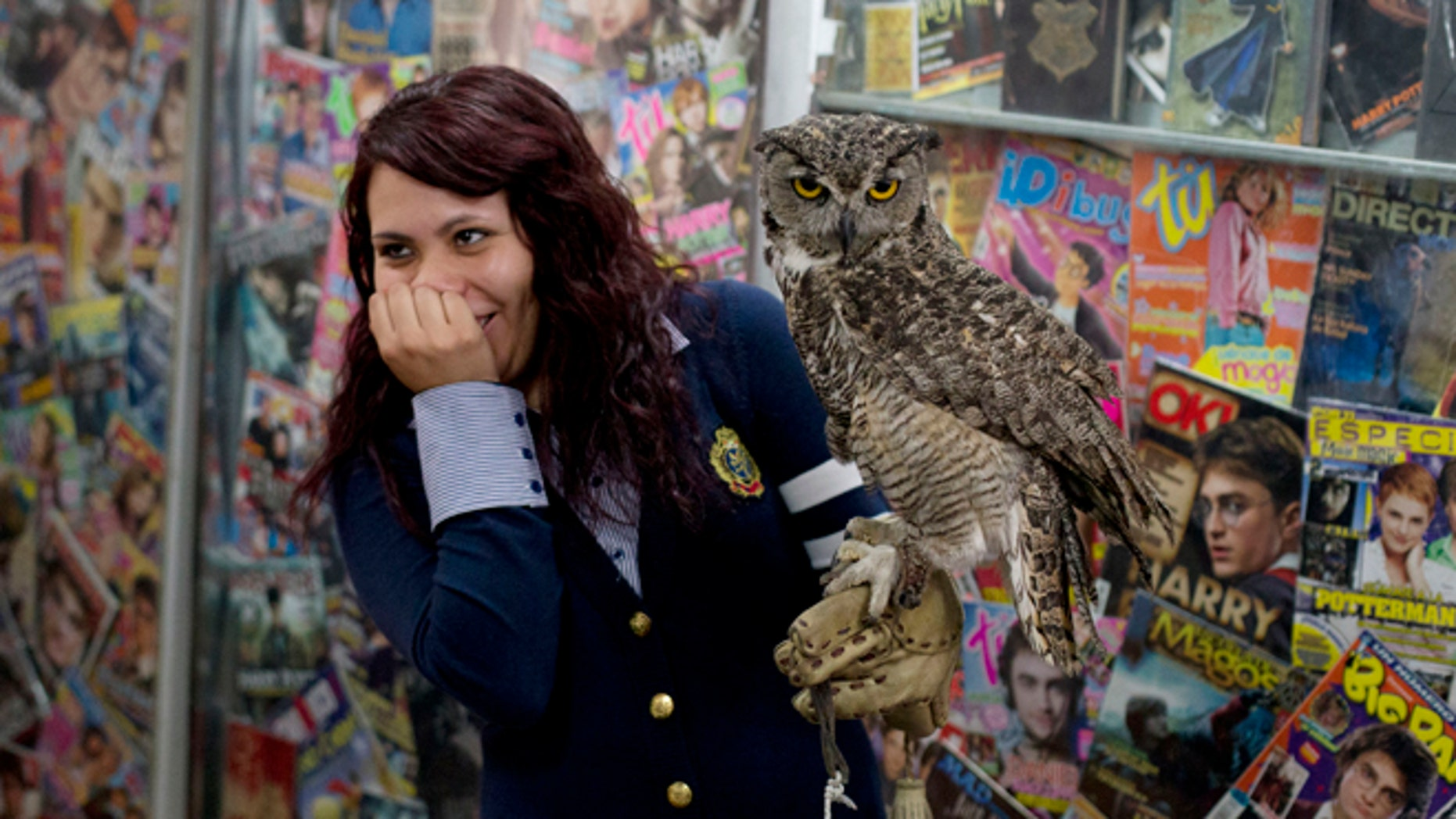 A Harry Potter fan reacts after a live owl bites her, inside an exhibition of the Guinness World Record holding collection of Harry Potter memorabilia, at the Mexican Museum of Antique Toys, in Mexico City, Friday, Feb. 27, 2015. Mexico's fan Menahem Asher Silva Vargas assembled the collection, which contains thousand objects, including figurines, wands, magazines, puzzles, and accessories. (AP Photo/Rebecca Blackwell)