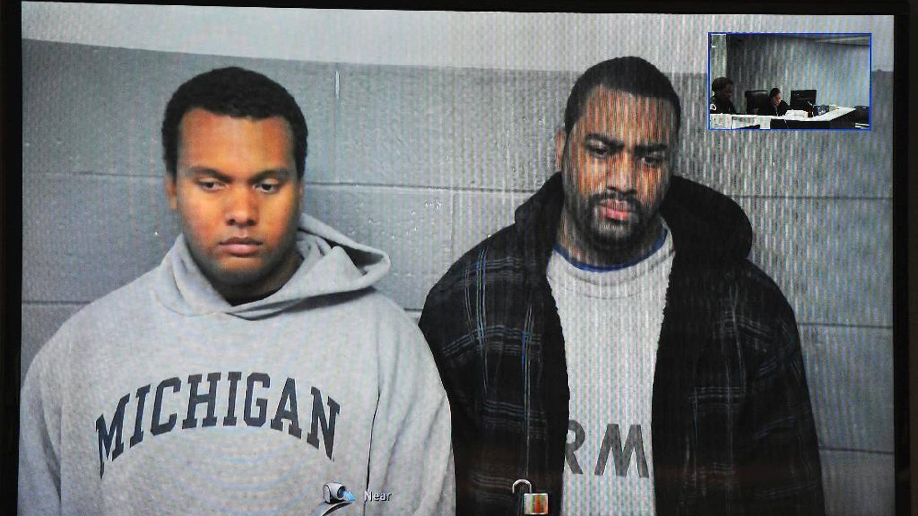 FILE- in this file image from Oct. 27, 2015, taken from video provided by the 36th District Court, Detroit police officers Charles Lynem, 28, left, and Chancellor Searcy, 31, are arraigned via video conference in Detroit. Detroit Police Chief James Craig says the two members of an elite police unit can return to work after being acquitted of stealing money from people they stopped on the street. A jury acquitted Officers Lynem and Searcy on Jan. 11, 2017. They had been suspended without pay. (Wayne County District Court/Detroit News via AP)