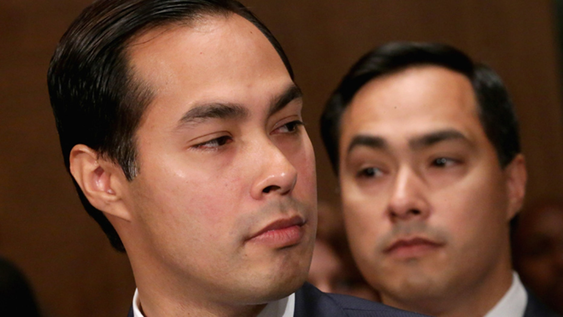 WASHINGTON, DC - JUNE 17:  Mayor Julian Castro (L) testifies during his confirmation hearing before the Senate Banking, Housing and Urban Affairs Committee with his twin brother, Rep. Joaquin Castro (D-TX), in the background June 17, 2014 in Washington, DC. The current mayor of San Antonio, Texas, Castro has not faced serious opposition in the Senate.  (Photo by Chip Somodevilla/Getty Images)