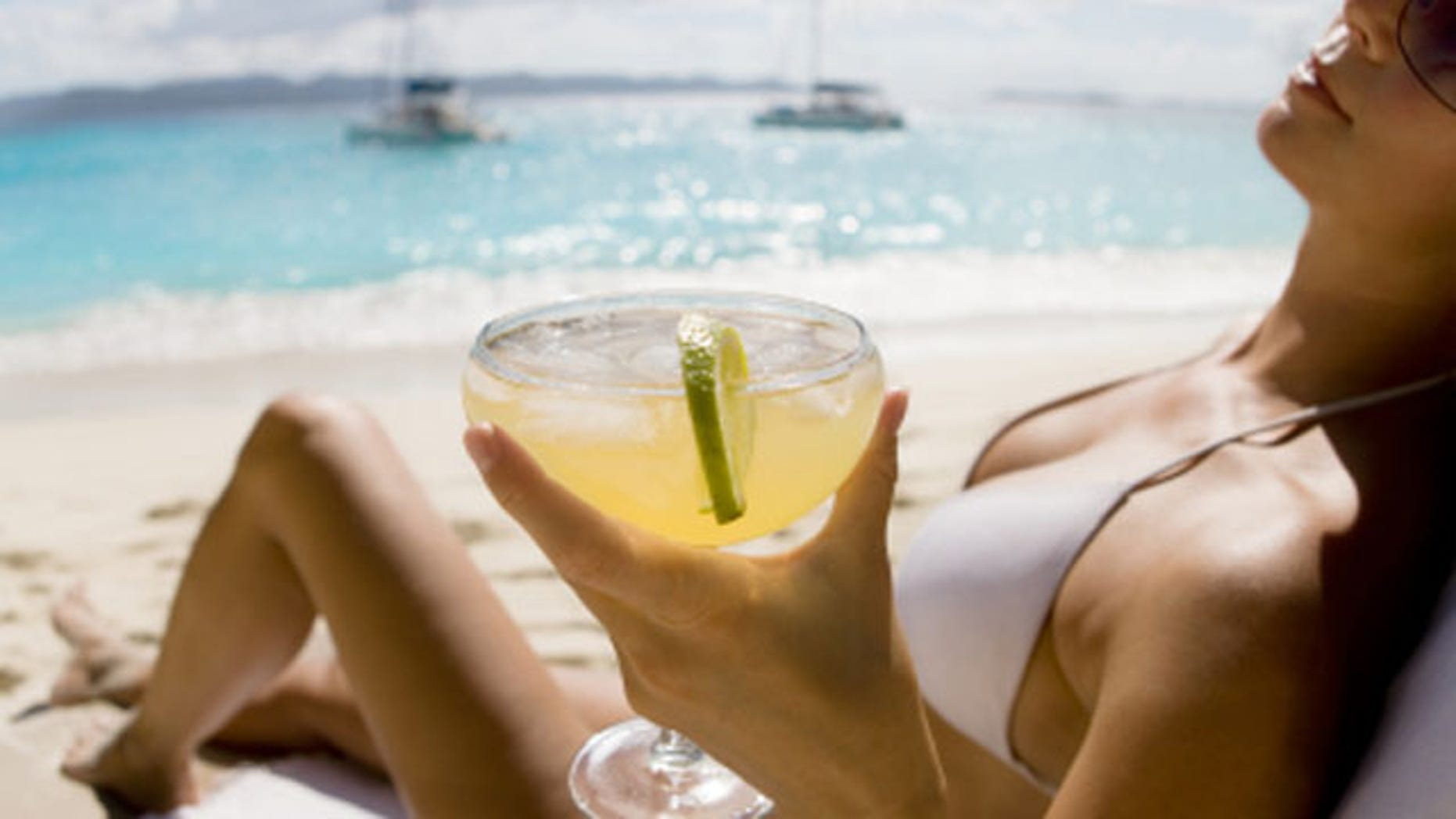 young woman relaxing at the beach in the Caribbean drinking margarita cocktail