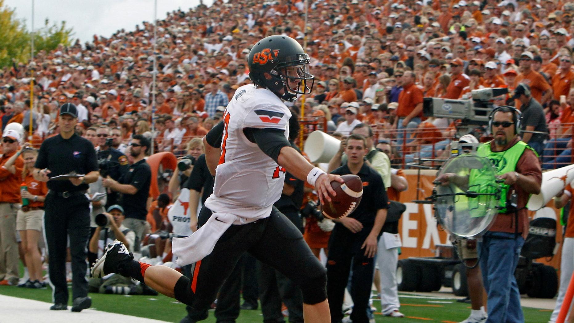 Oklahoma State quarterback Clint Chelf scores a touchdown against Texas during the second quarter of an NCAA college football game Saturday, Nov. 16, 2013, in Austin, Texas. (AP Photo/Michael Thomas)