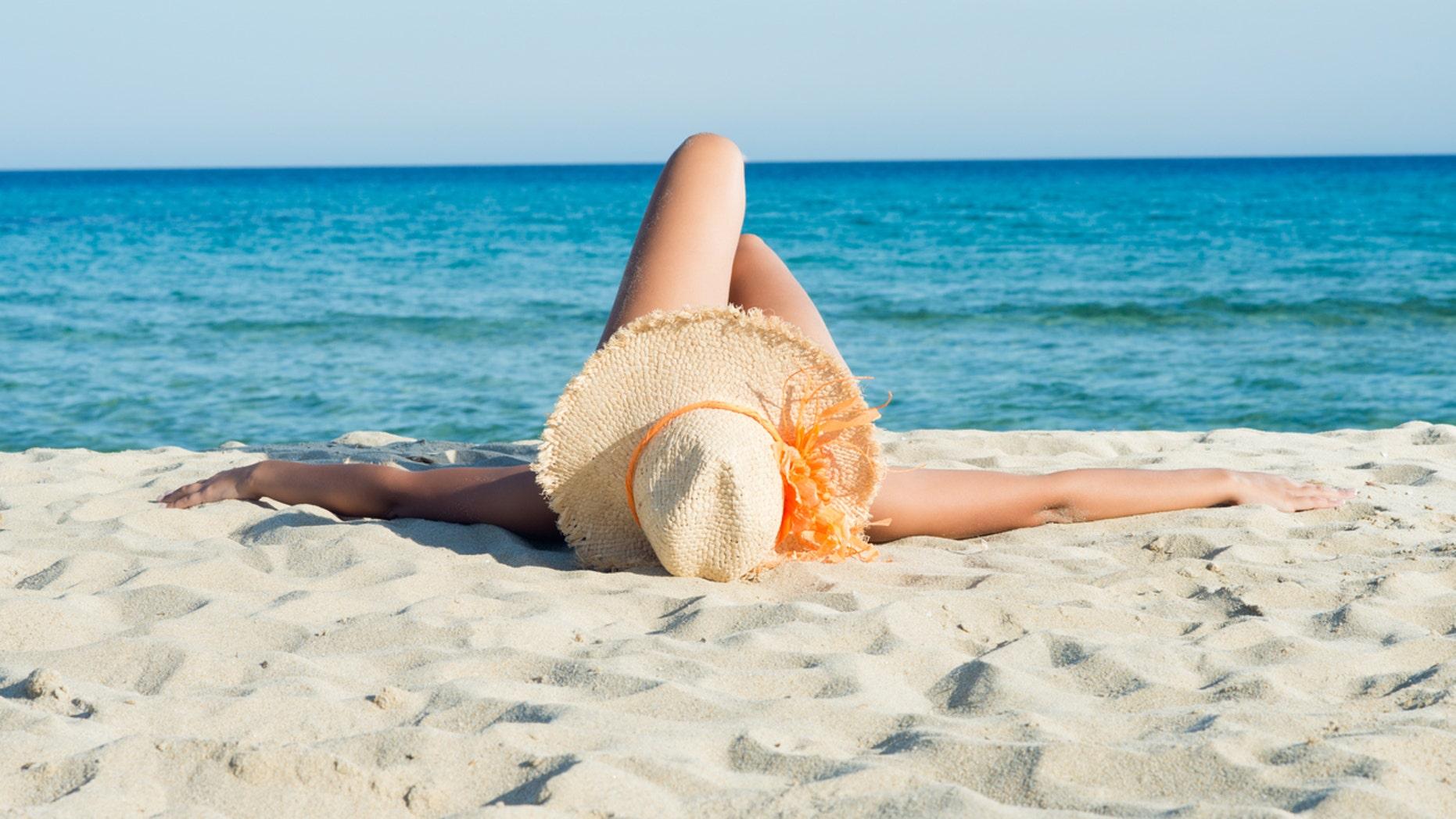 Young Woman Enjoying Sunbath On White Beach.