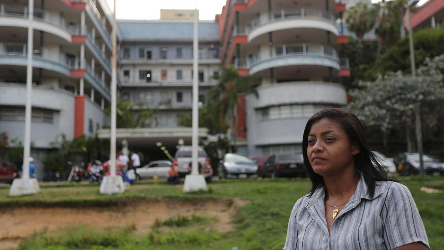 """Carmen Bolivar, a University Hospital nurse, poses for a photo outside of the Hospital in Caracas, Venezuela, Wednesday, Aug. 13, 2014. Last June Carmen stood paralyzed by fear next to a patient's brother as a gunman walked in on them. University Hospital, a sprawling, poorly maintained building that resembles a noisy bus station, guards still go unarmed, there is no surveillance system and a worn sign reading """"No entrance"""" is the only thing stopping a person from walking into the operating area. Security workers say they would run if confronted by an armed intruder. (AP Photo/Ariana Cubillos)"""