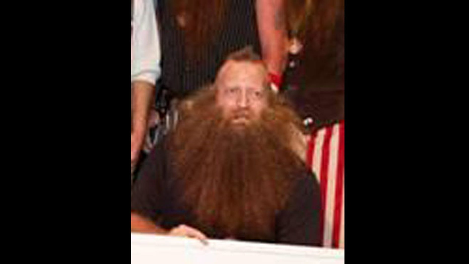 """Jeff Langham accepts a check for winning the """"Just for Men National Beard & Moustache Championships."""""""