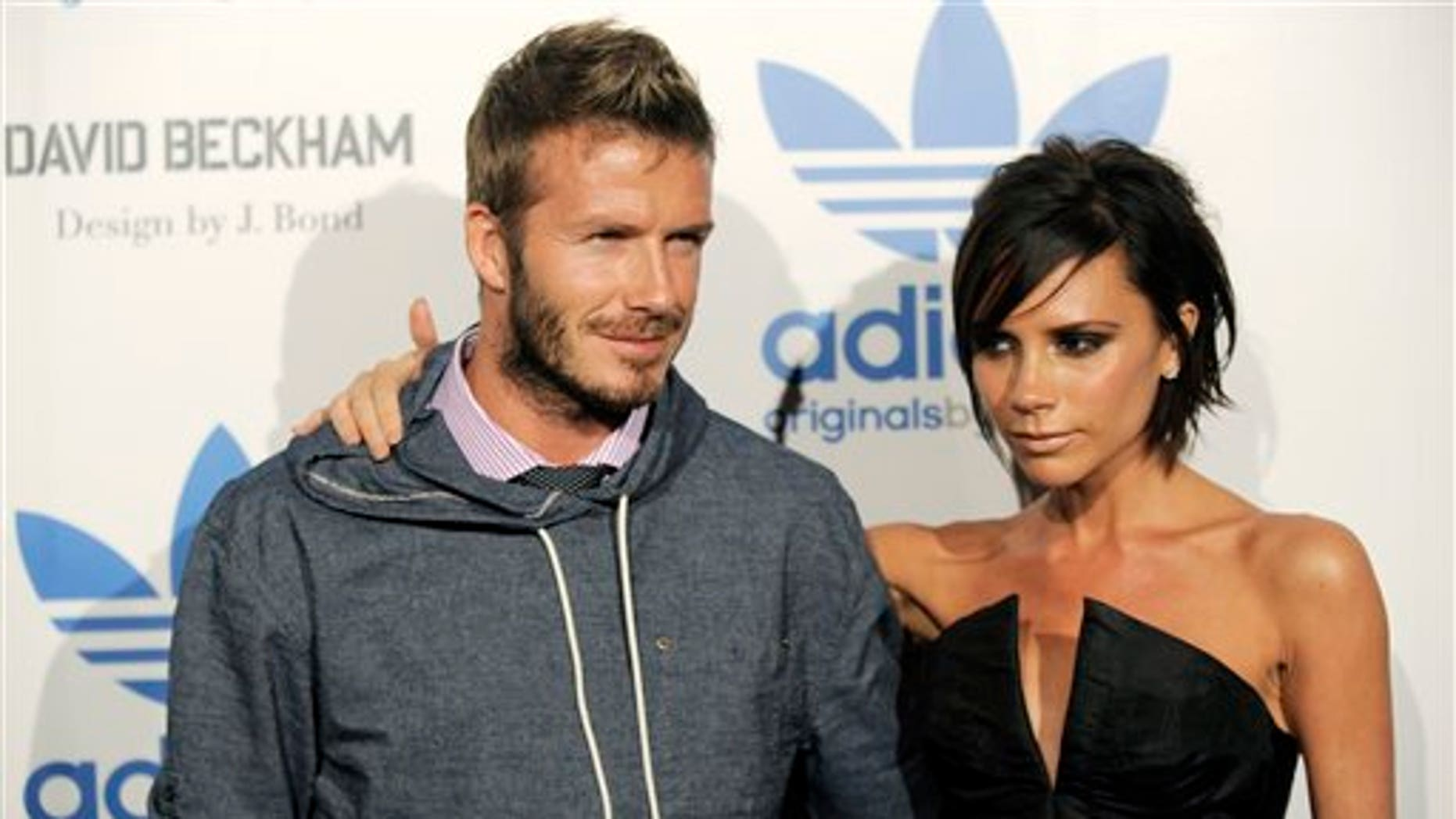 David Beckham and his wife Victoria arrive at an event to celebrate the launch of the Adidas Originals by Originals David Beckham clothing line designed by James Bond, Wednesday, Sept. 30, 2009, in Los Angeles. (AP Photo/Chris Pizzello)