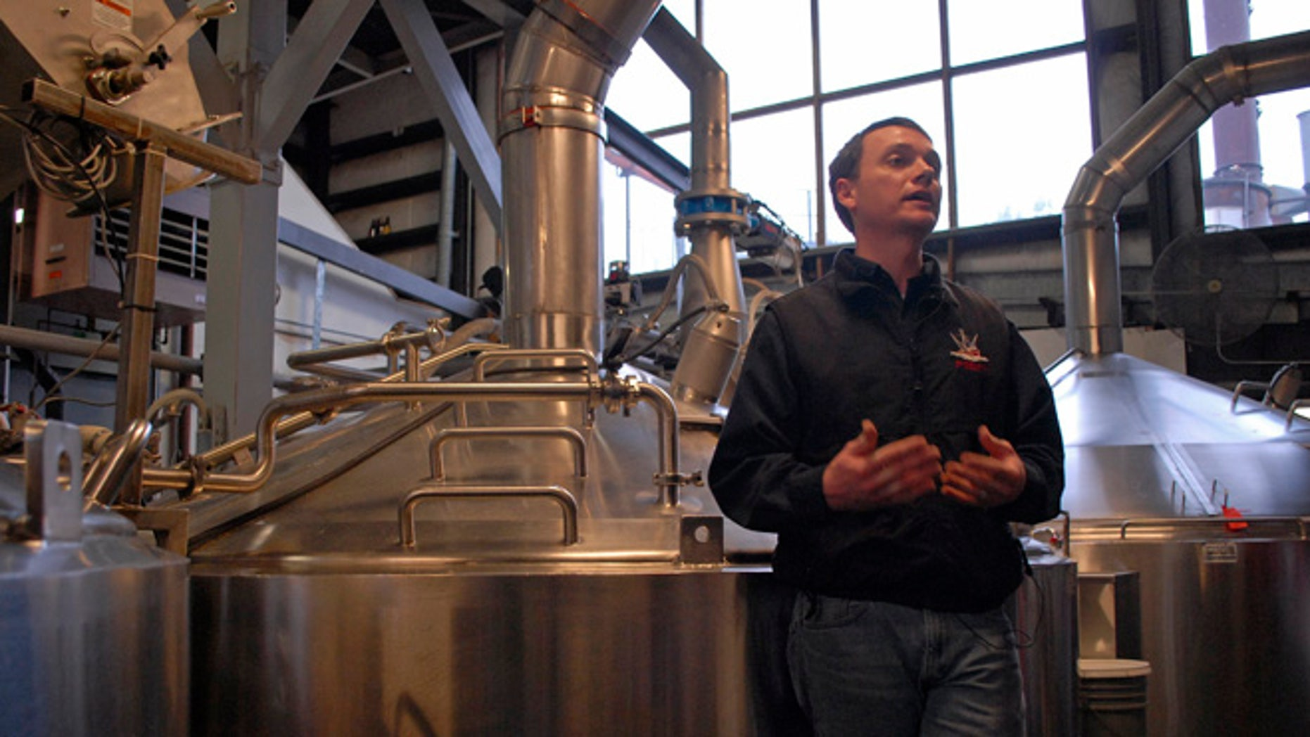 Brandon Smith, the Alaskan Brewing Co.'s brewing operations and engineering manager, speaks to reporters about the company's new boiler system. The brewery has installed a unique boiler system that burns the company's spent grain the accumulated waste from the brewing process into steam which powers the majority of the plant's operations.