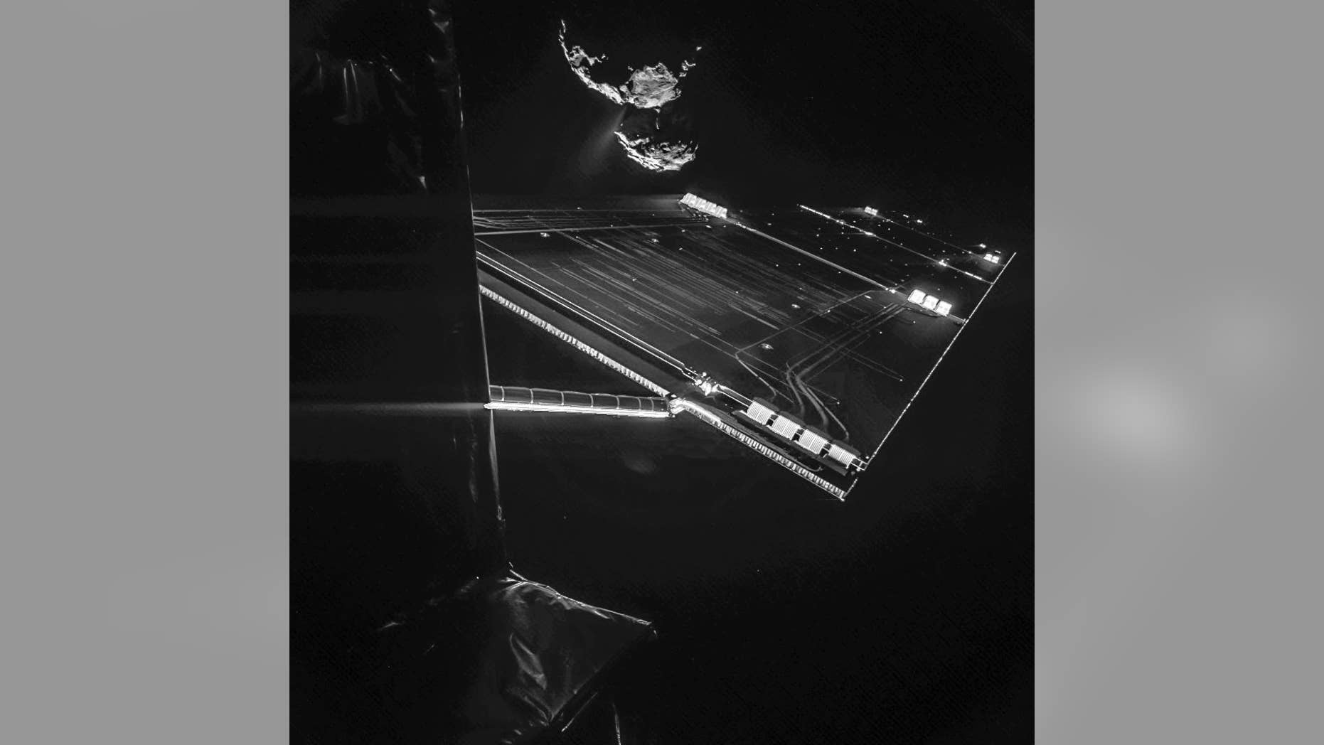 The image composed of two different images and provided by the European Space Agency ESA on Wednesday, Oct. 15, 2015 shows parts of the spacecraft Rosetta in front of the comet 67P/Churyumov–Gerasimenko from a distance of about 16 km from the surface of the comet. The image was taken on 7 October and captures the side of the Rosetta spacecraft and one of Rosetta's 14 m-long solar wings, with the comet in the background.  Two images with different exposure times were combined to bring out the faint details in this very high contrast situation. The comet's active 'neck' region is clearly visible, with streams of dust and gas extending away from the surface. (AP Photo/ESA)
