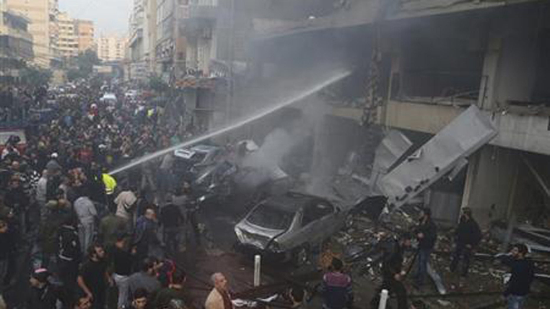 People gather as firefighters attempt to extinguish a fire at the site of an explosion in Beirut's southern suburbs, Jan. 2, 2014. (Reuters)