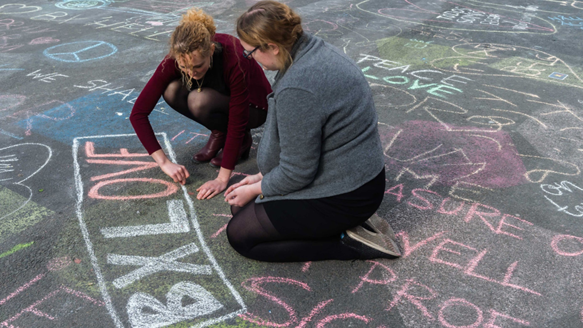 March 22, 2016: Two people write solidarity messages in chalk outside the stock exchange in Brussels.