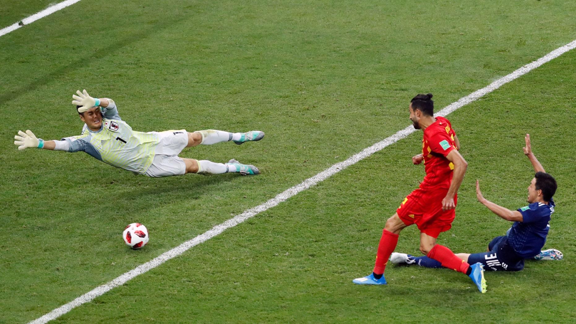 Belgium's Nacer Chadli scores the winning goal past Japanese keeper Eiji Kawashima in the World Cup last 16 match.