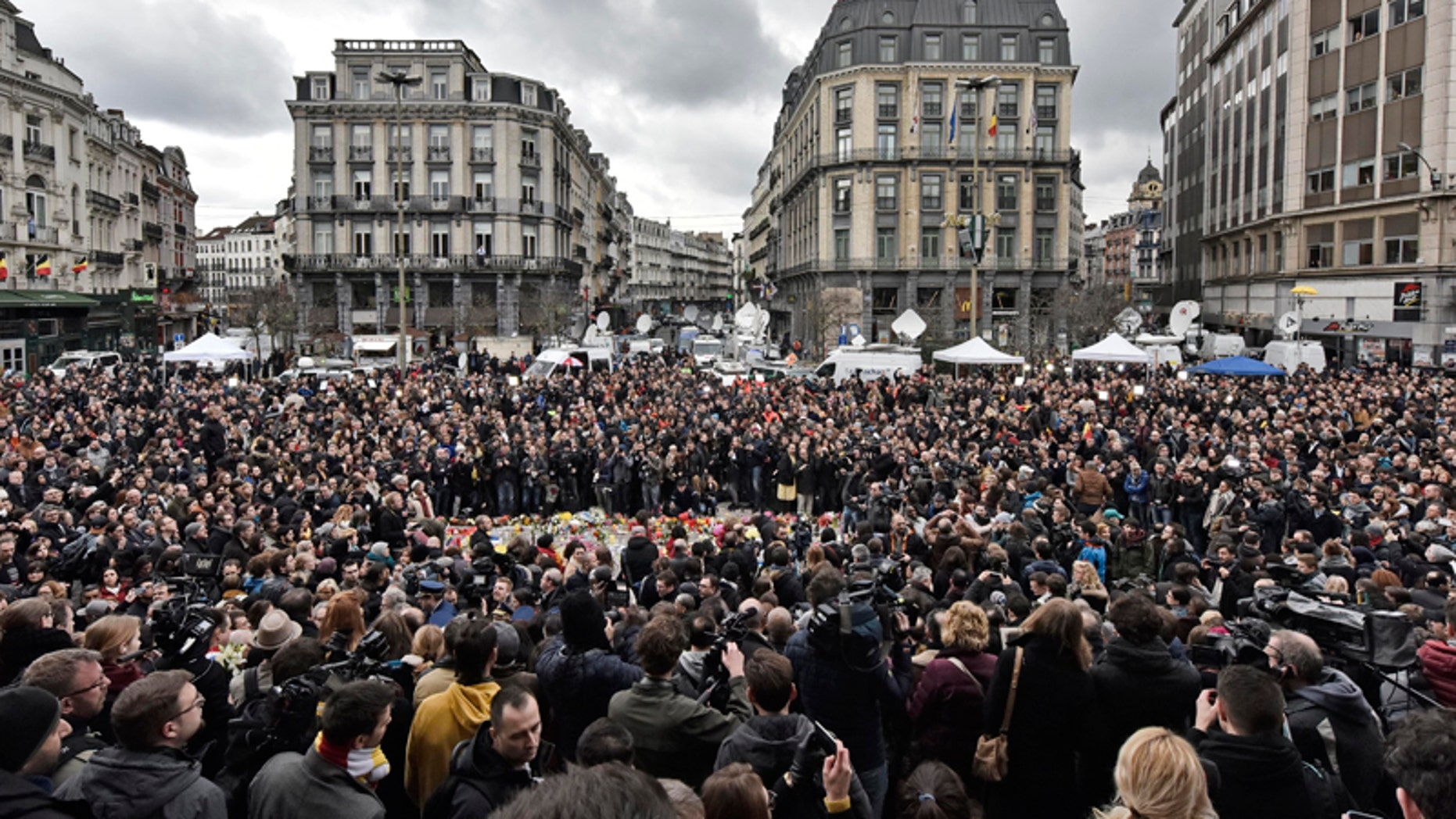 People observe a minute of silence at the Place de la Bourse in the center of Brussels, Wednesday, March 23, 2016. Bombs exploded yesterday at the Brussels airport and one of the city's metro stations Tuesday, killing and wounding scores of people, as a European capital was again locked down amid heightened security threats. (AP Photo/Martin Meissner)