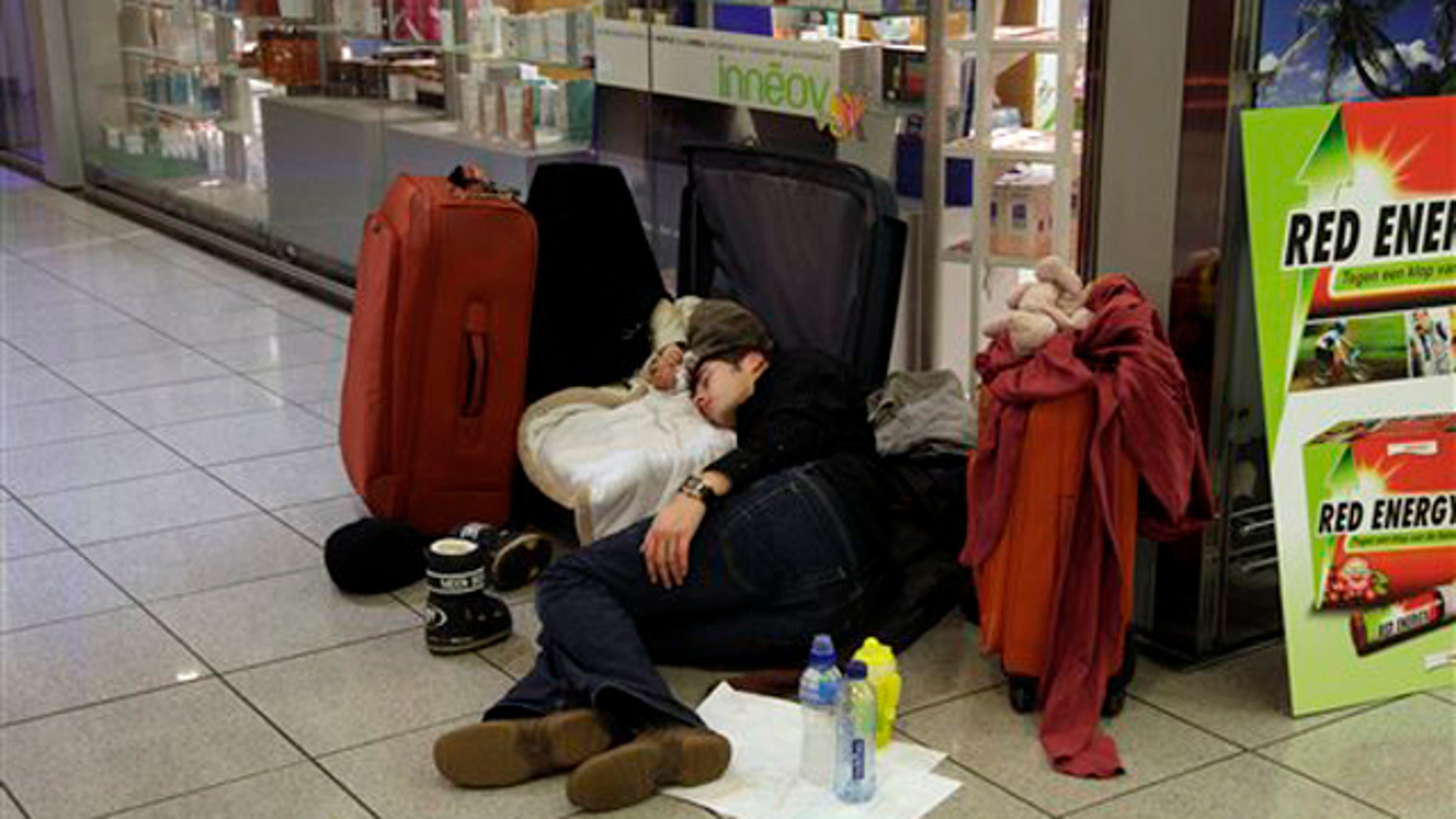 Dec. 24, 2010: A man sleeps with his infant in a suitcase at Zaventem airport in Brussels. A new batch of snow caused air traffic chaos in Belgium on Friday, with its main airport either canceling or delaying many flights.