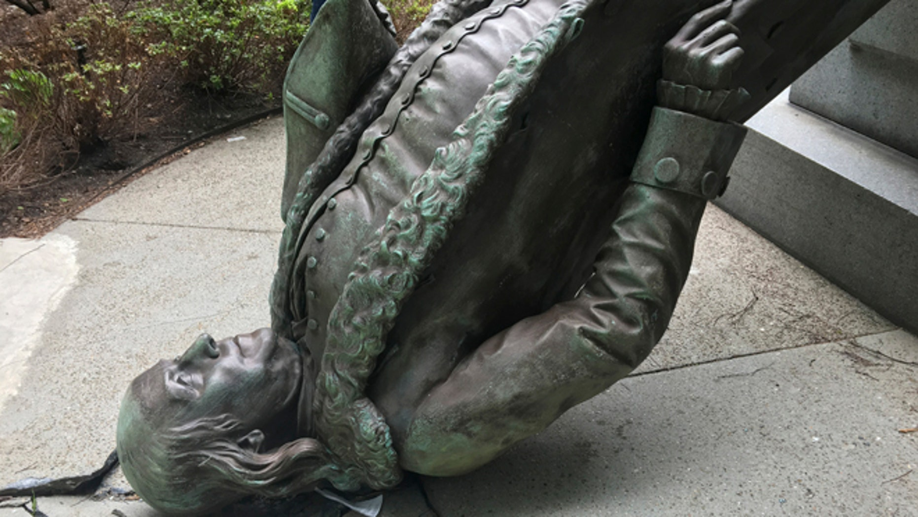 In this photo released by the City of Boston Mayor's office, a statue of Benjamin Franklin lies on the concrete outside where it landed when knocked off its pedestal outside Old City Hall