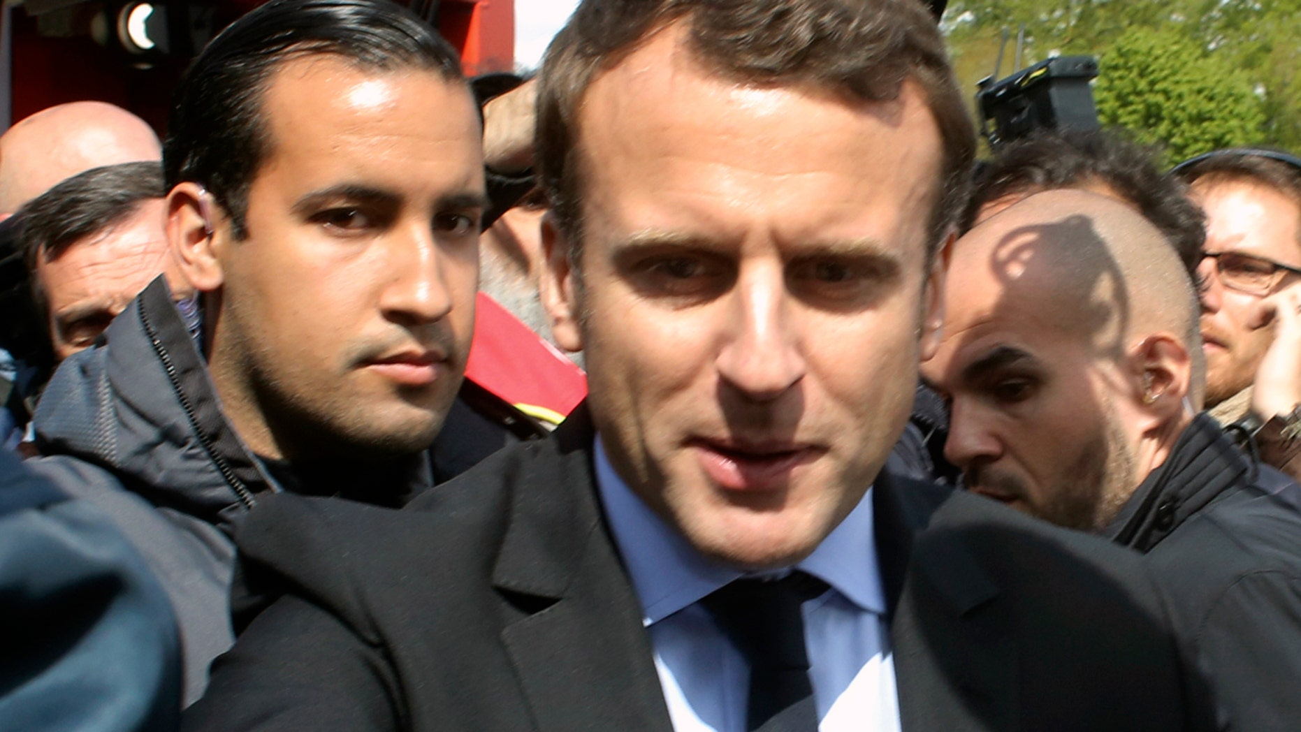 Alexandre Benalla stands with Emmanuel Macron during last year's French presidential election campaign. Benalla, now a top security aide to Macron, was caught on camera beating a May Day protester.