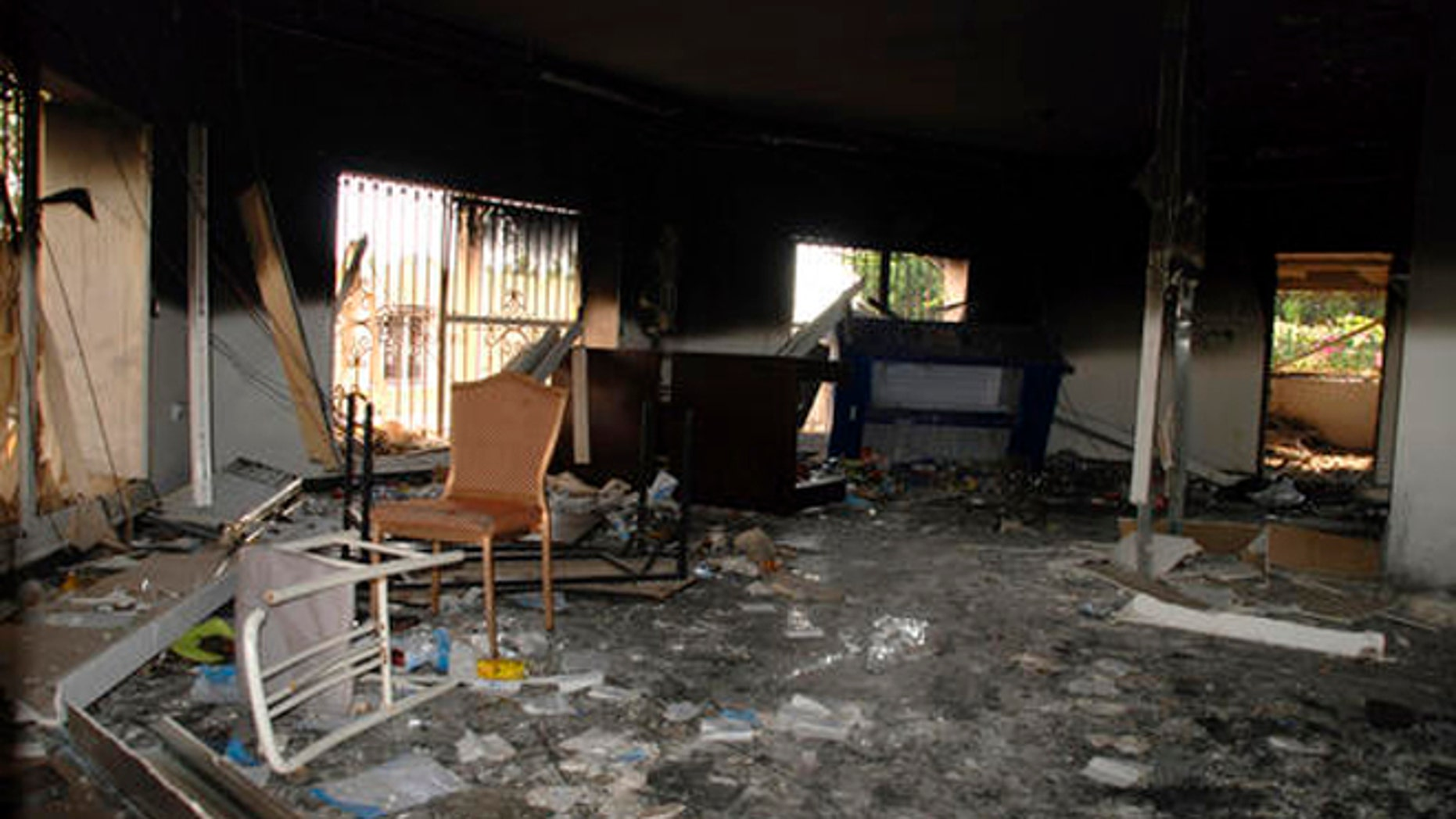 In this Sept. 12, 2012 file photo, glass, debris and overturned furniture are strewn inside a room in the gutted U.S. consulate in Benghazi, Libya, after an attack that killed four Americans, including Ambassador Chris Stevens.