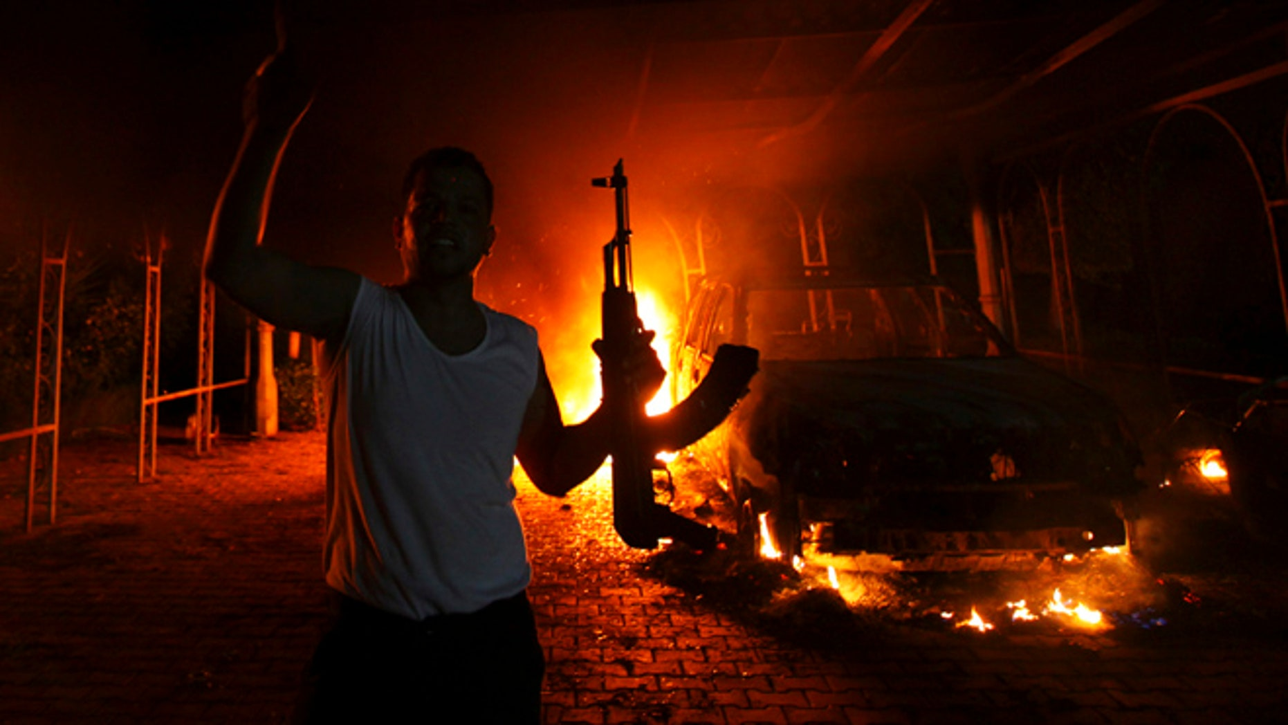 Sept. 11, 2012: A protester reacts as the U.S. Consulate in Benghazi is seen in flames during a protest by an armed group.