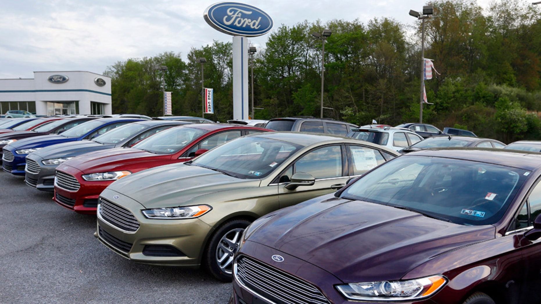 In this Wednesday, May 8, 2013 photo, new 2013 Ford Fusions are seen at an automobile dealer in Zelienople, Pa. U.S. auto sales slowed slightly in June 2014 but still maintained a healthy pace despite a record-setting string of safety recalls at General Motors and a slowdown in truck sales at Ford. Ford's U.S. sales chief John Felice said sales picked up at the end of June as automakers started promoting Independence Day sales. (AP Photo/Keith Srakocic)