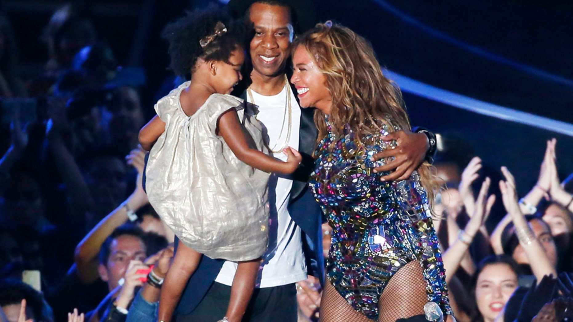 Beyonce smiles with Jay-Z and daughter Blue Ivy after accepting the Video Vanguard Award on stage during the 2014 MTV Video Music Awards in Inglewood, California August 24, 2014.